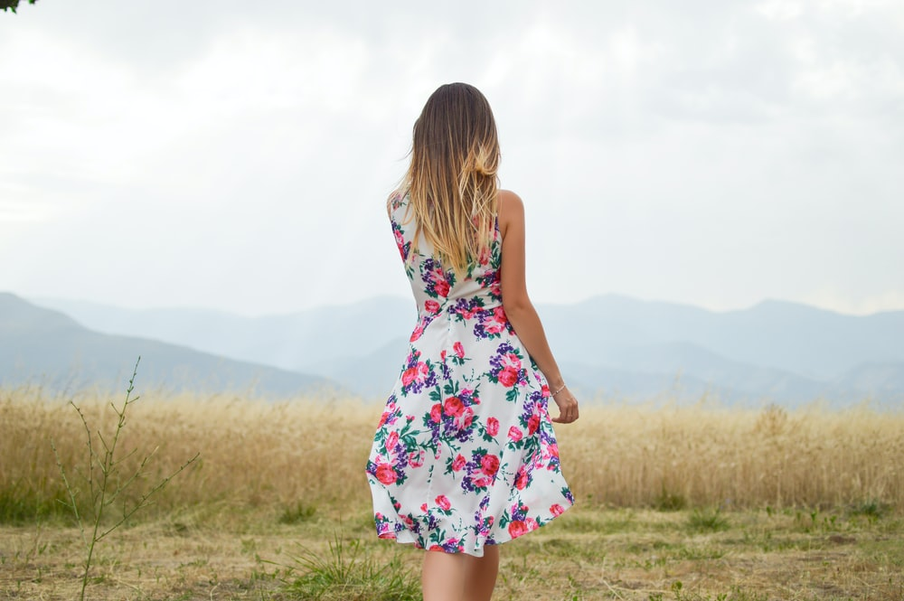 woman wearing white, purple, and pink floral dress standing near brown leaf grass field during daytime