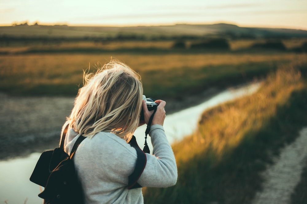 selective focus photography of woman taking picture during daytime