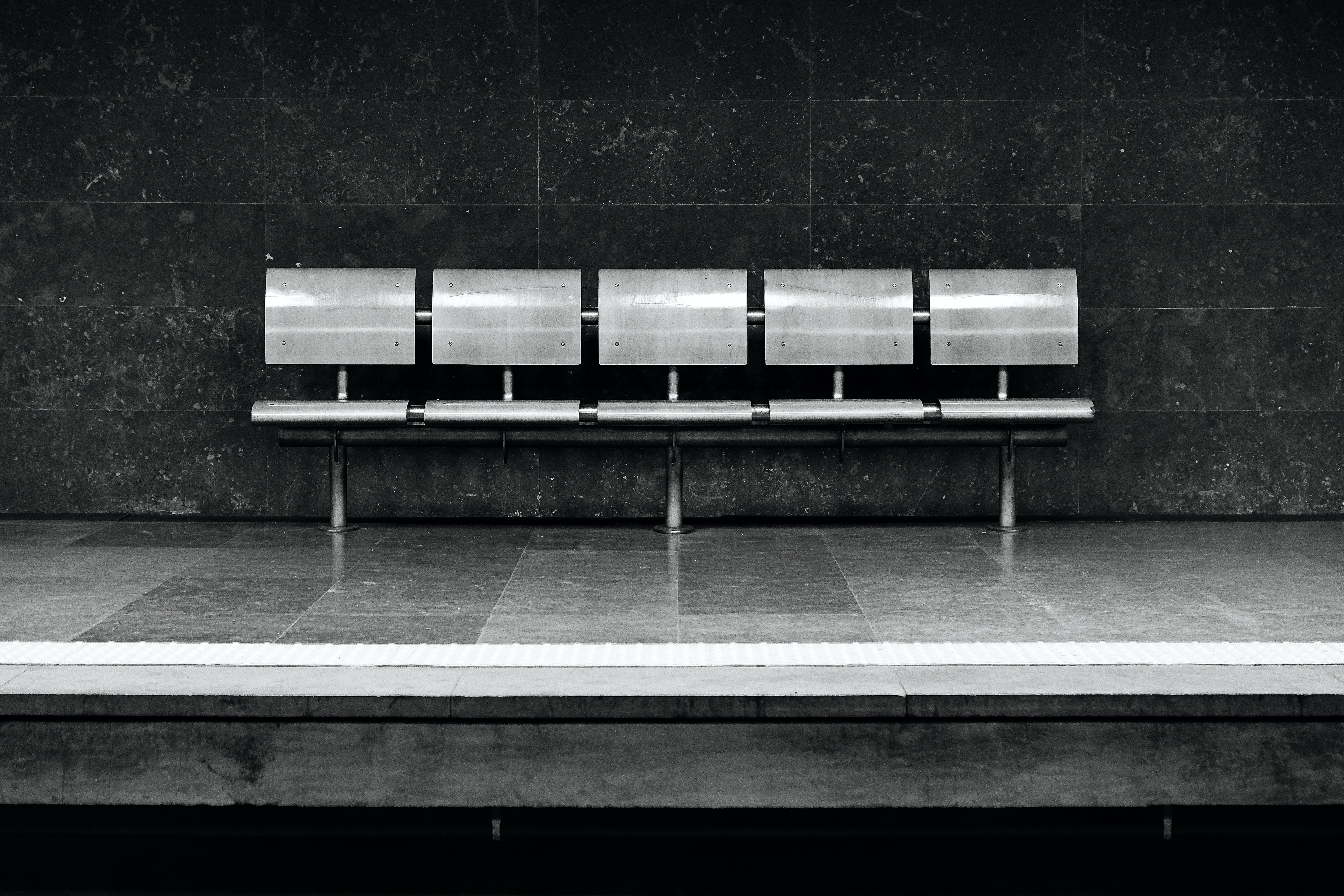 A black-and-white shot of a glossy metal bench at a subway platform