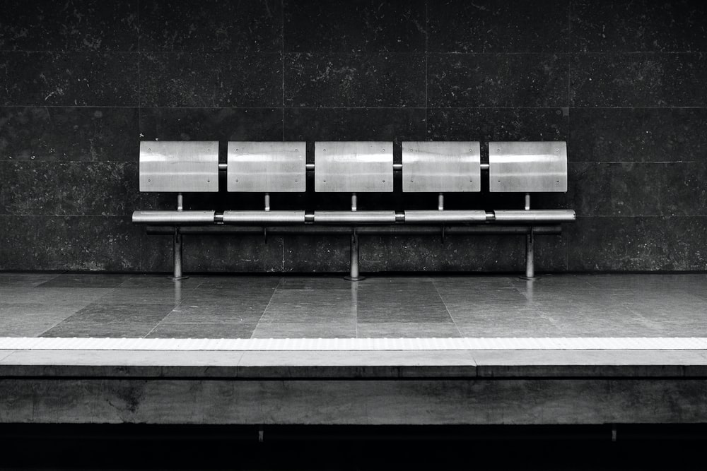 grayscale photo of silver 5-seat gang chair