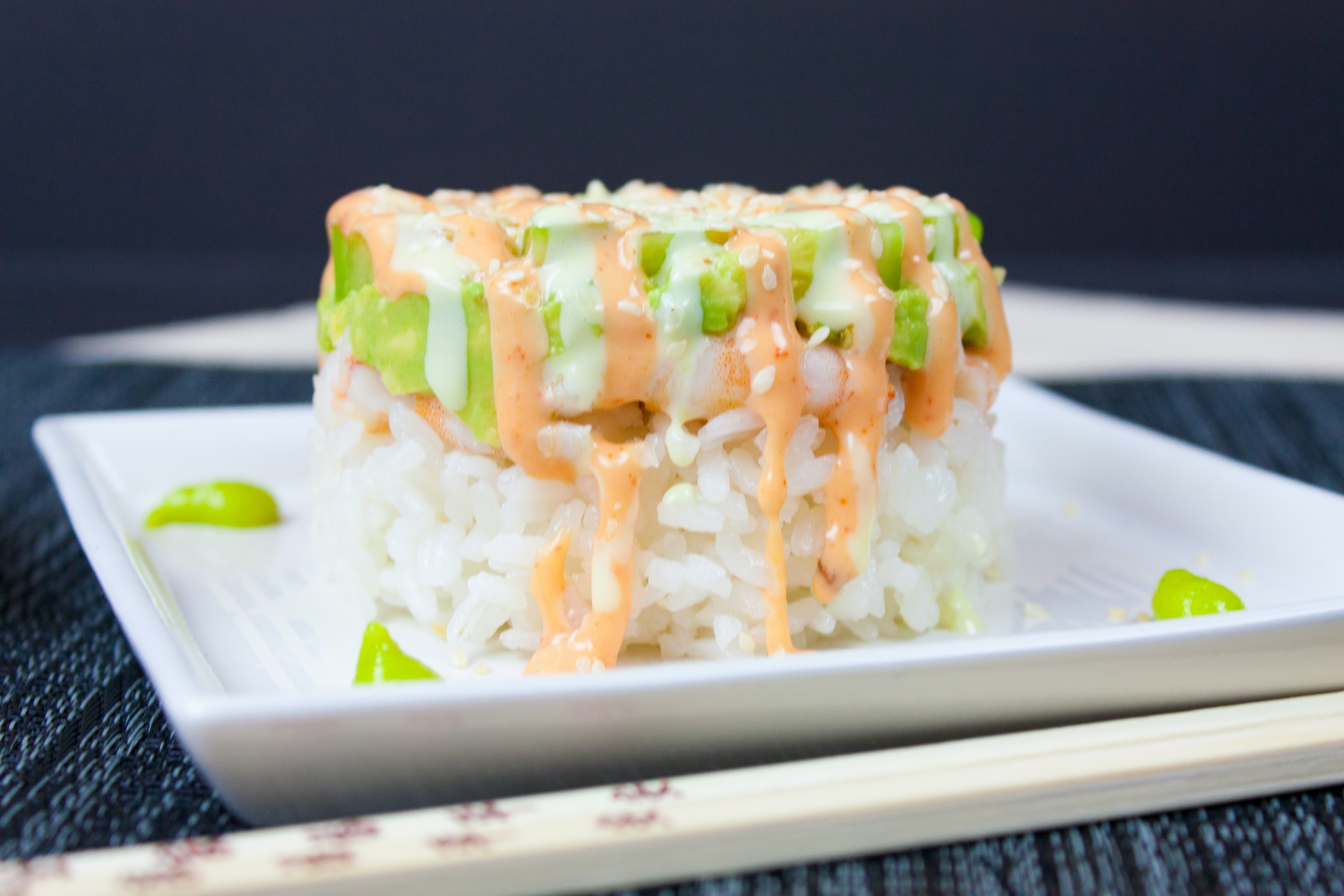 Asian dish consisting of a rice mount with vegetables, shrimp, sesames and a special sauce drizzled over