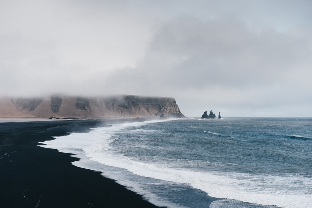black sand near body of water under the cloudy sky during daytime