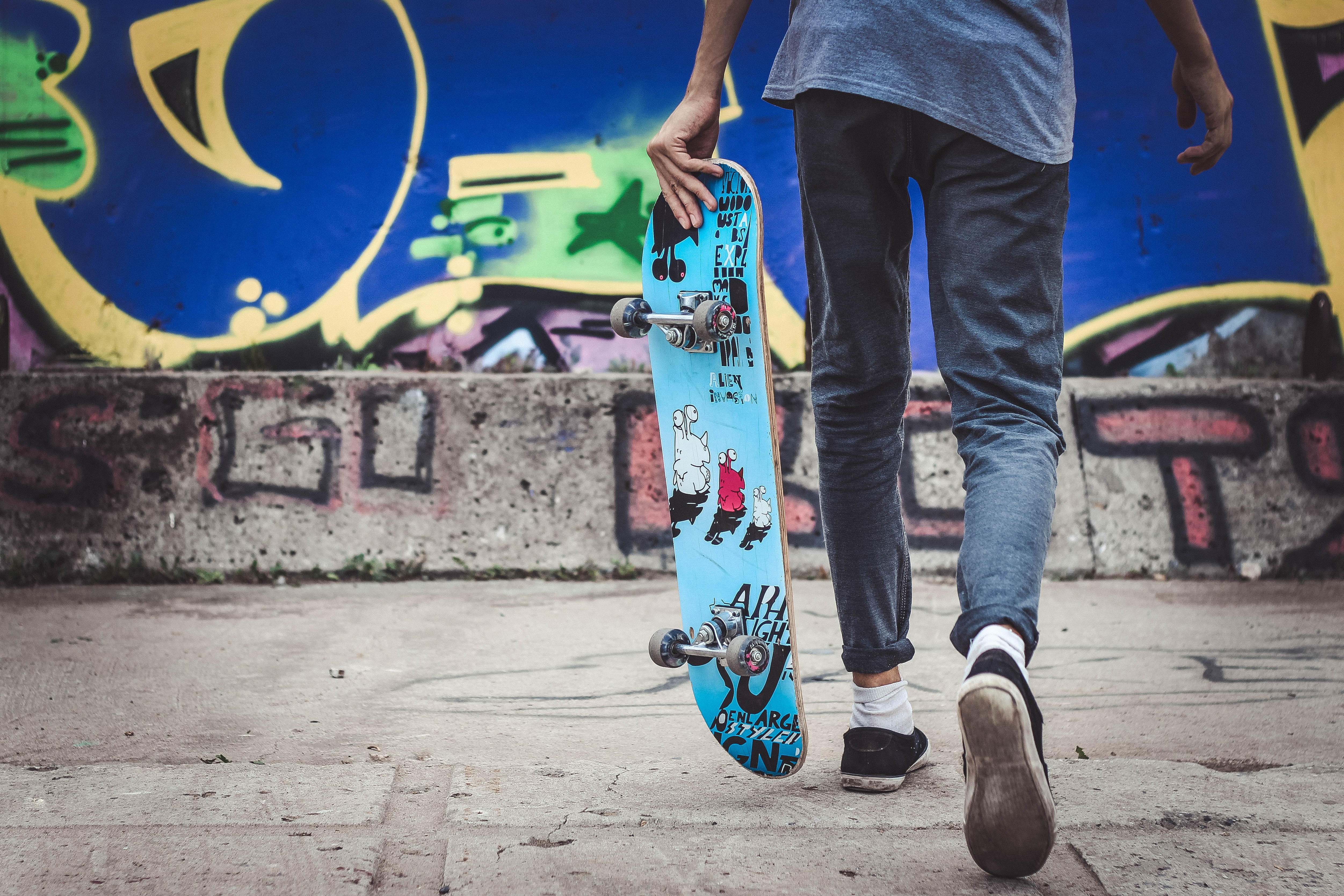 A person holds a decorated skateboard in front of a blue graffitied wall
