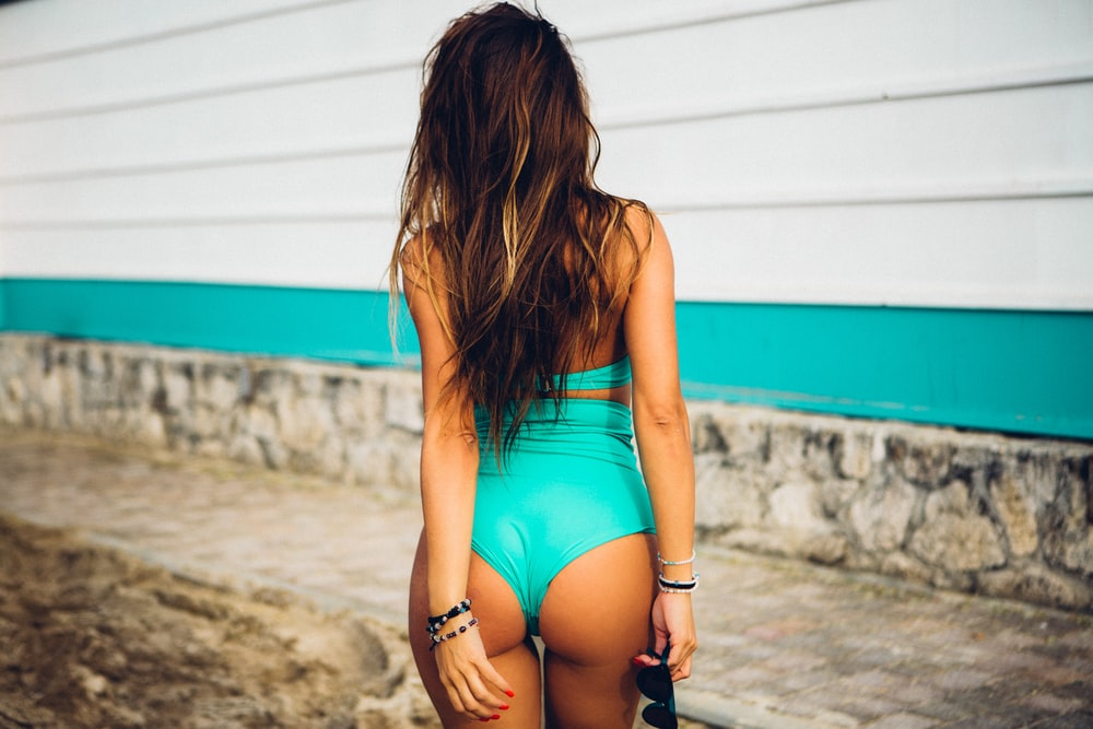 woman wearing swimsuit facing back standing on road