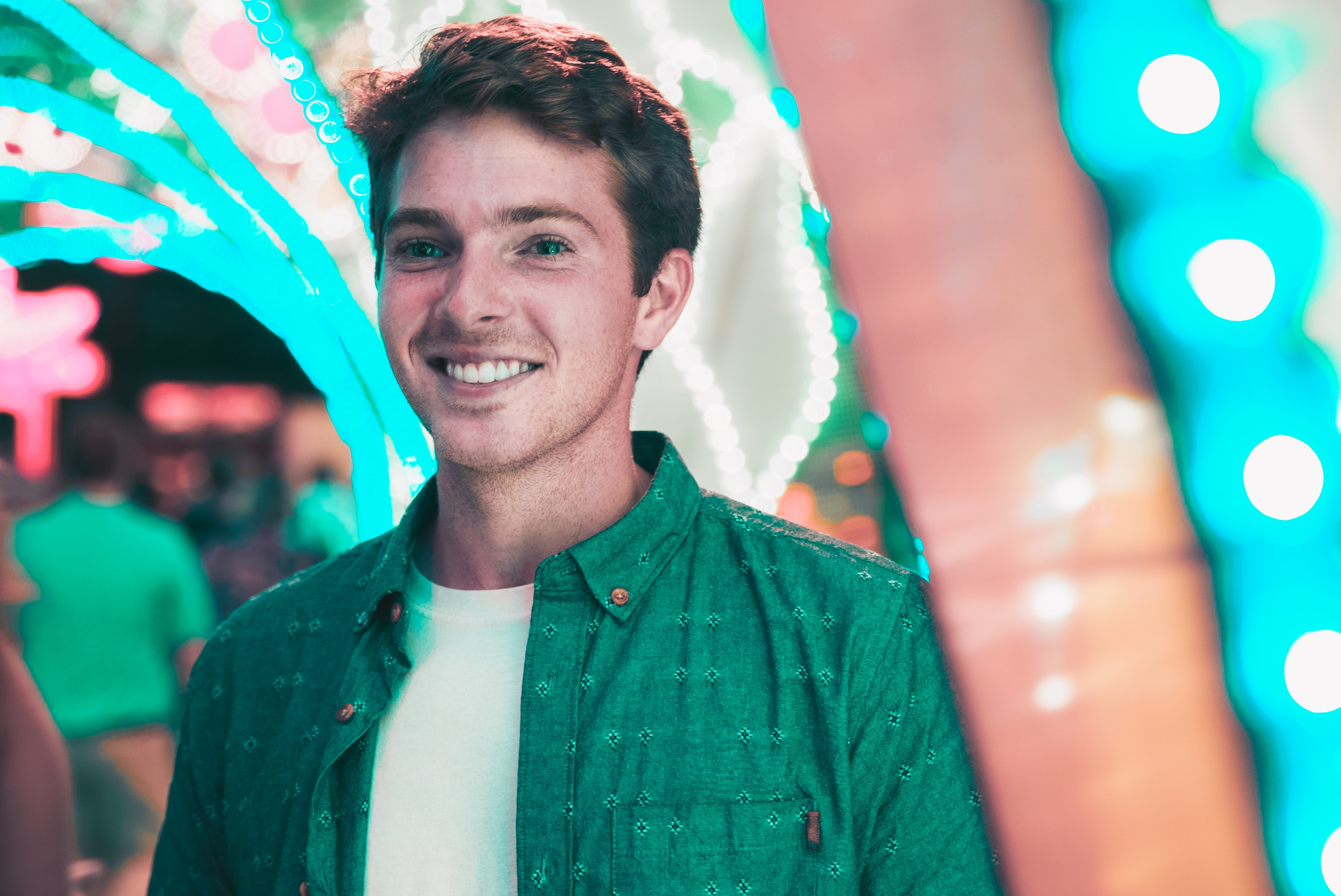 A portrait of a smiling young man in front of a light display in Philadelphia