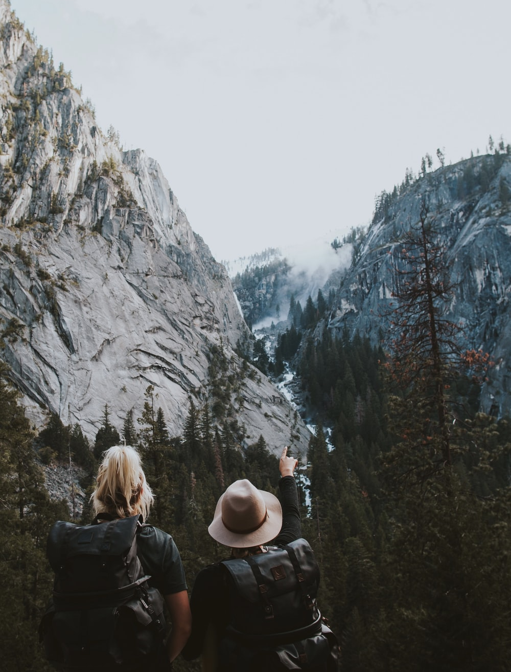two human standing between the mountains