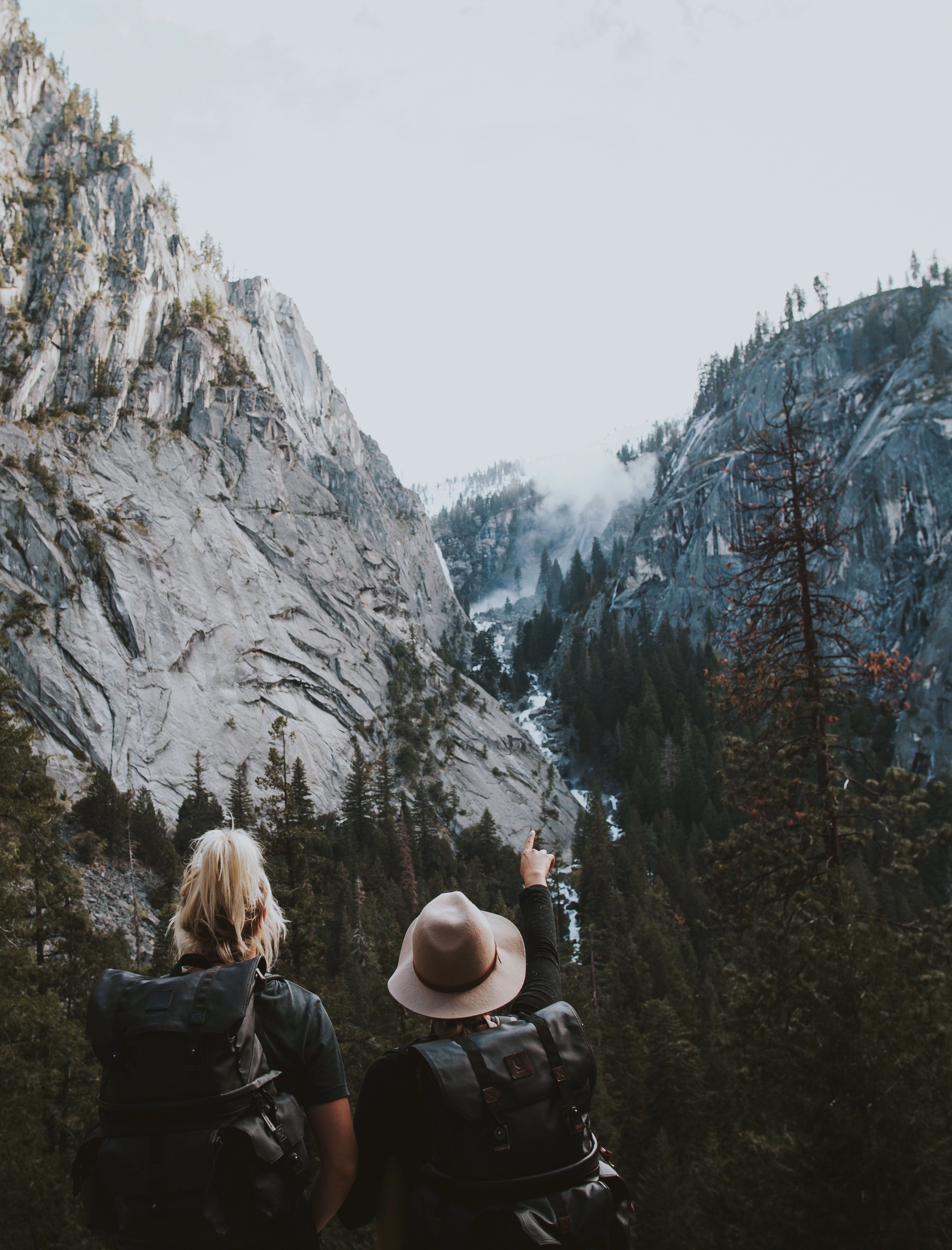 Two women with large backpacks in a mountain pass in Yosemite