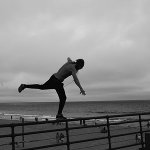 man standing on metal railing overlooking beach shoreline under gray cloudy skies at daytime
