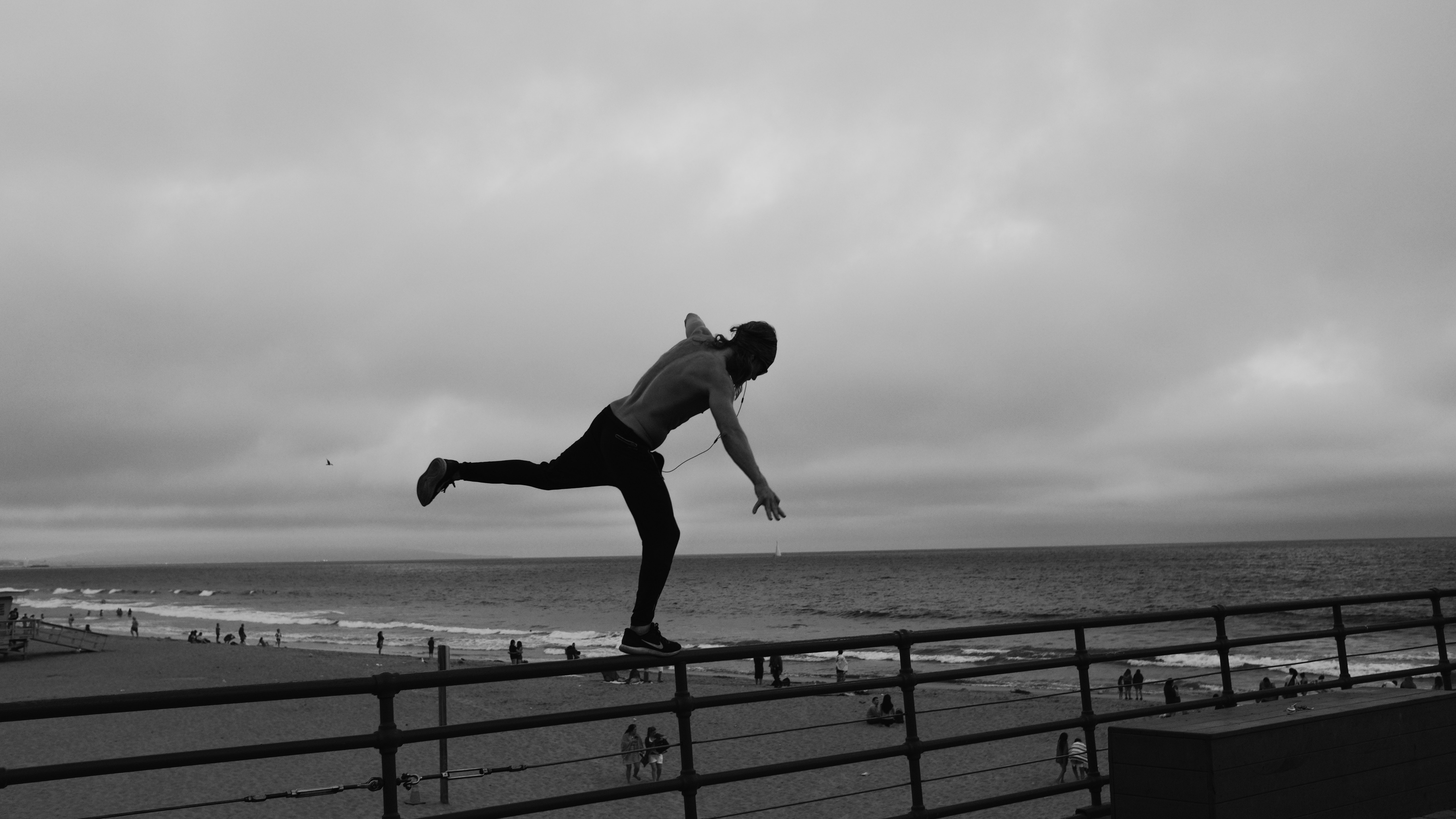 Black and white person balancing on barrier at Santa Monica Pier near the ocean