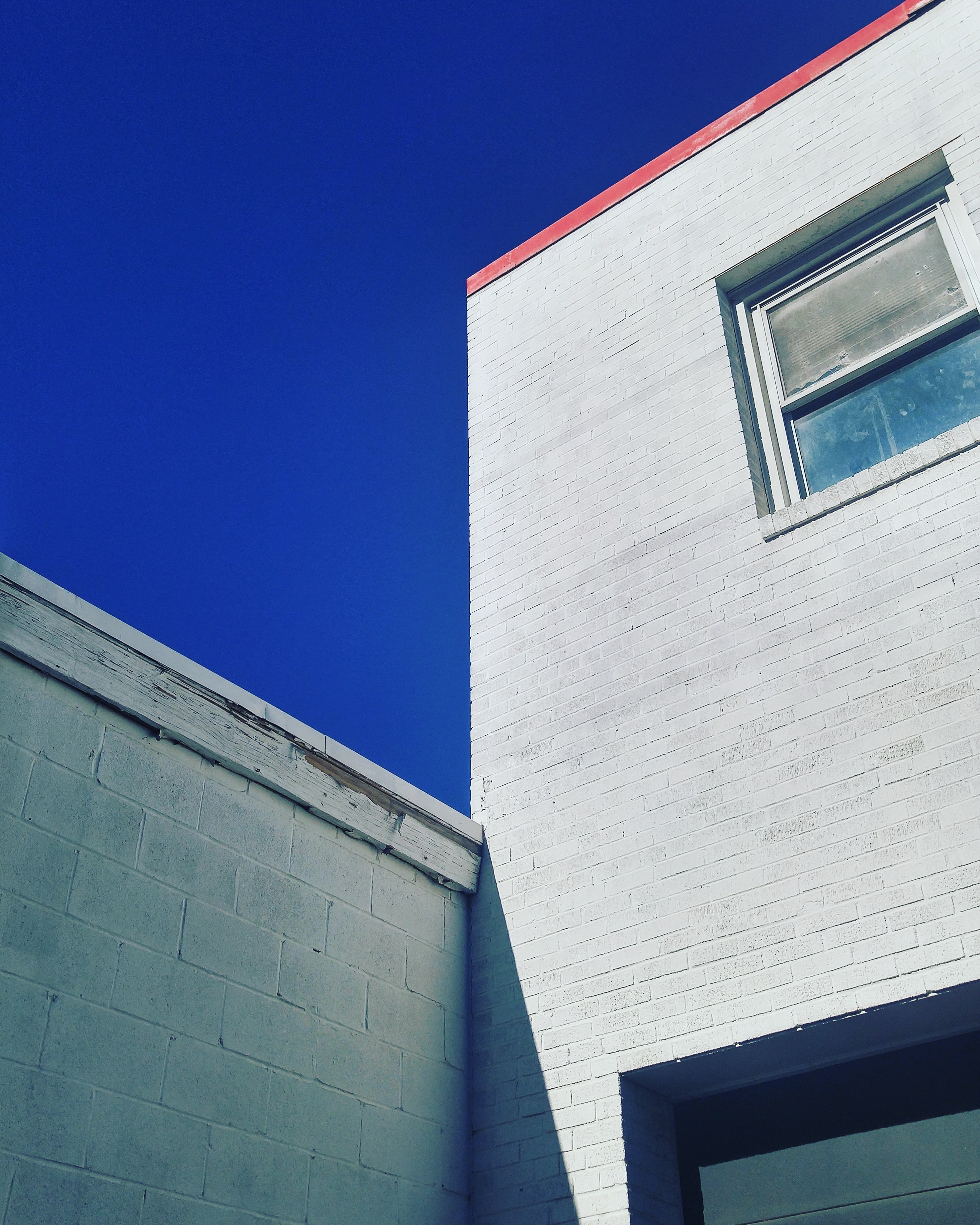 Concrete building exterior with red roof and a window with a dark blue sky