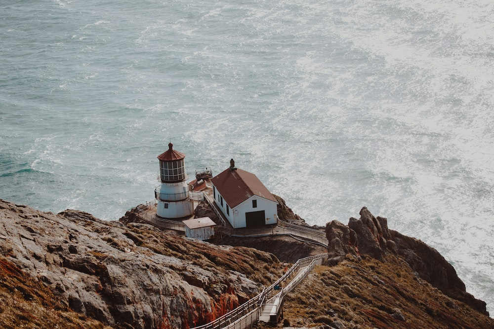 aerial photography of white and brown concrete house beside lighthouse on gray mountain cliff near body of water at daytime