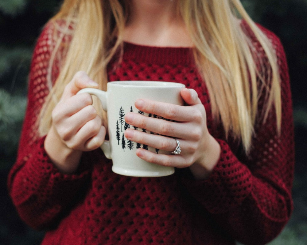 Woman wearing a red sweater holding a cozy mug of coffee