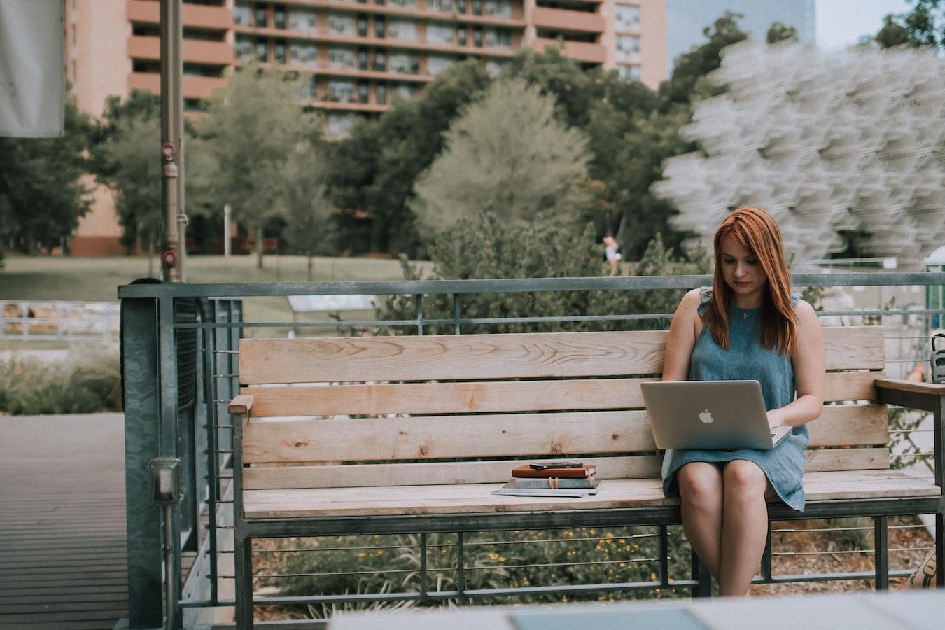 mamá emprendedora trabajando desde un banco del parque para conciliar