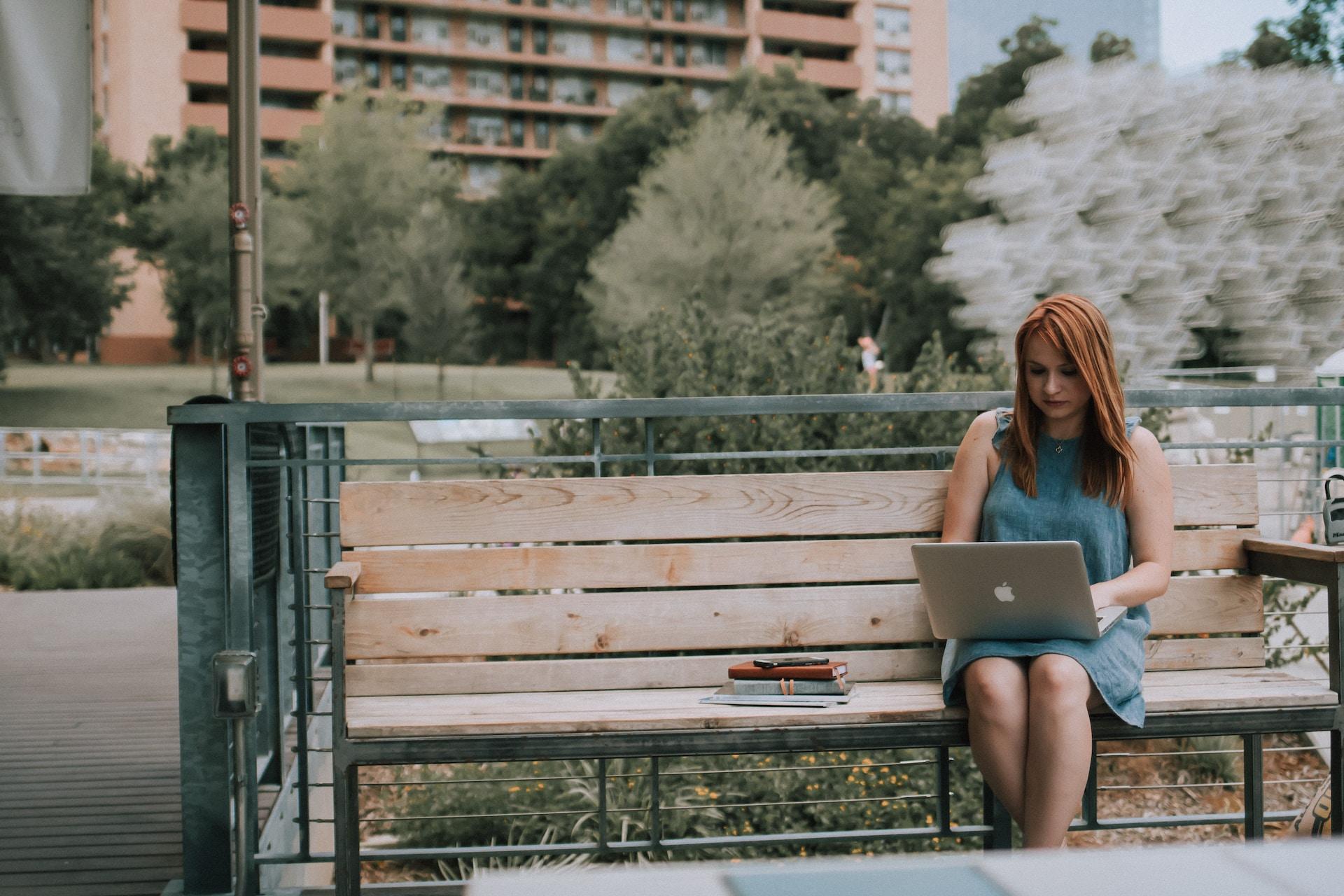 woman sitting on bench white using MacBook Pro