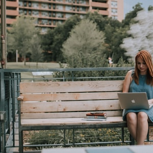 woman sitting on bench white using MacBook Pro