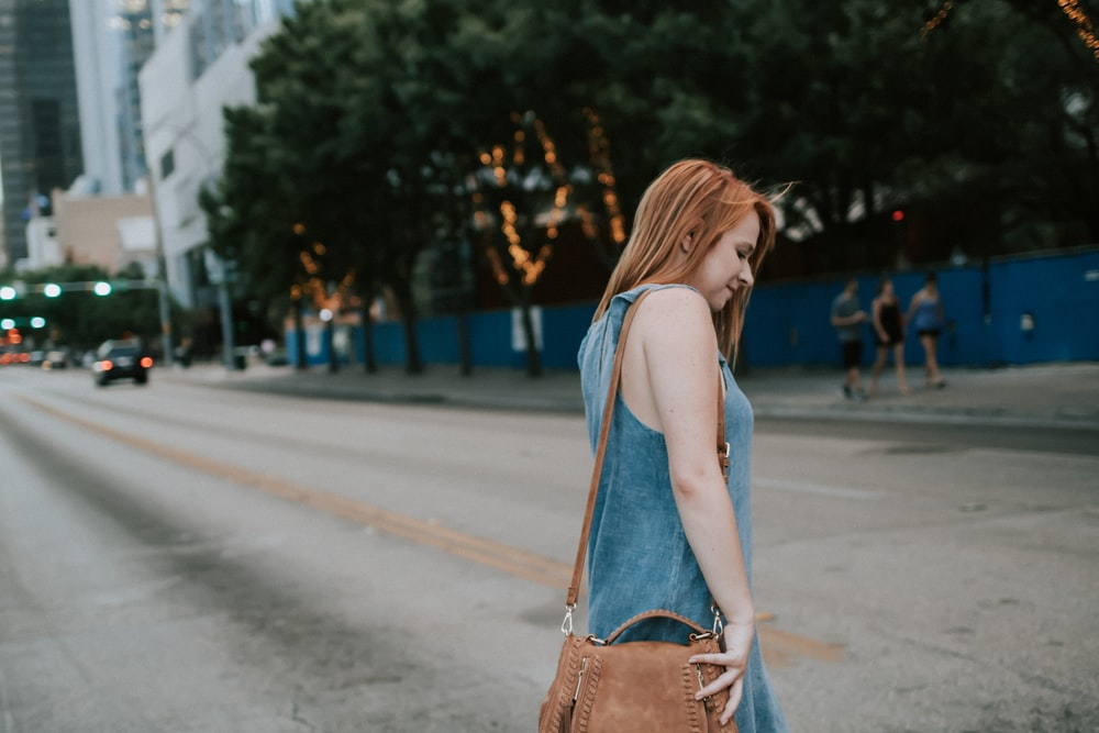 woman crossing the street during daytime photo