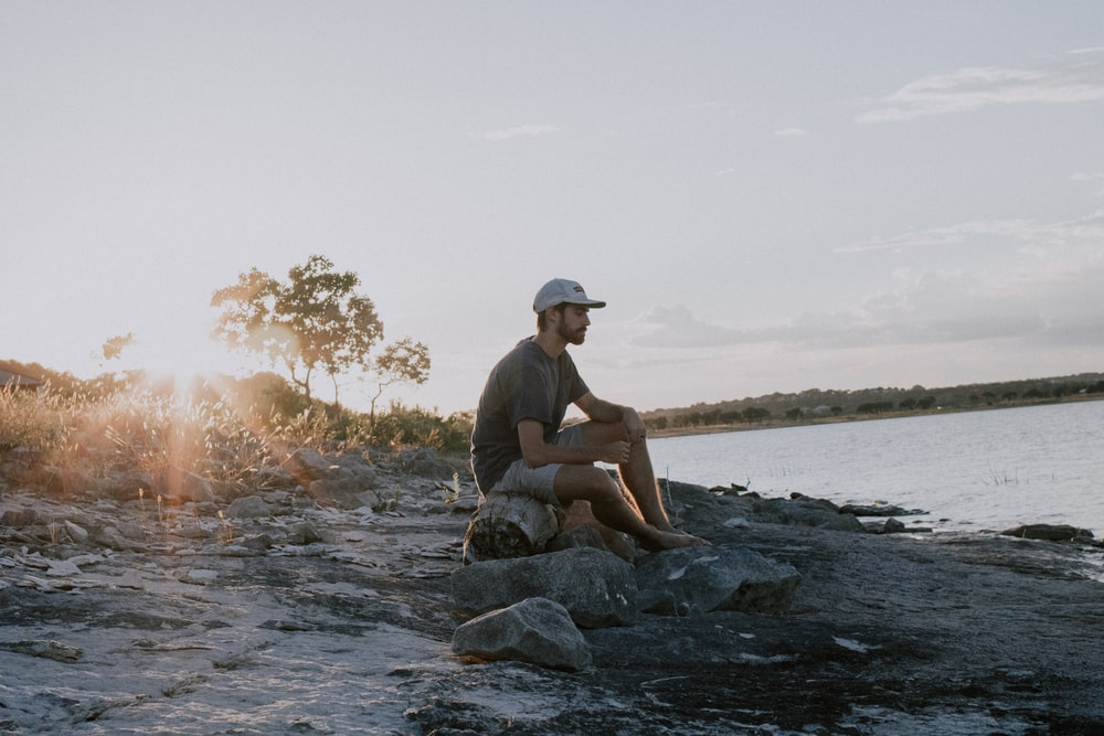 man sitting on rock near body of water during daytime