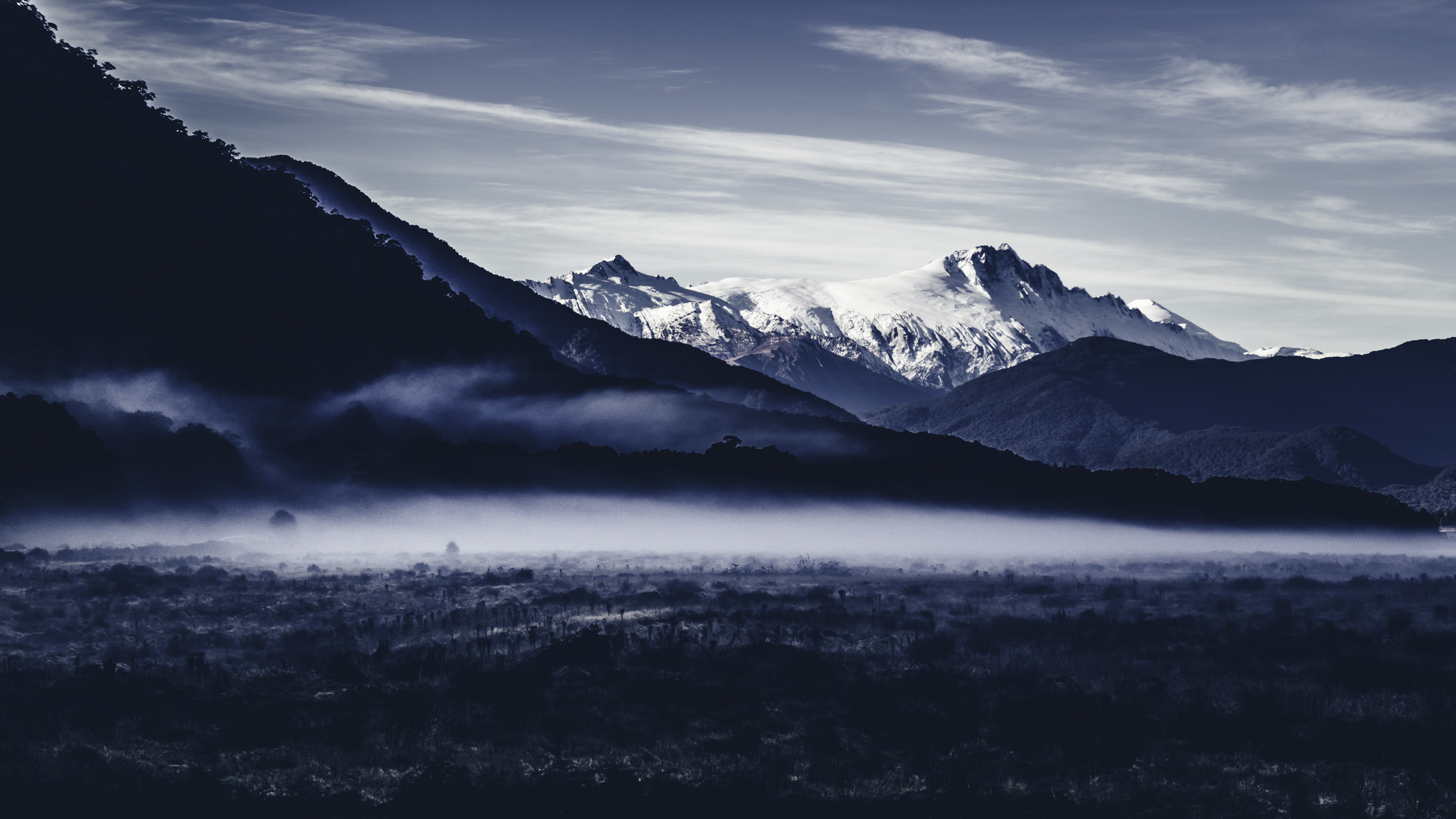 Mist on the valley beneath snowy mountains in a blue landscape