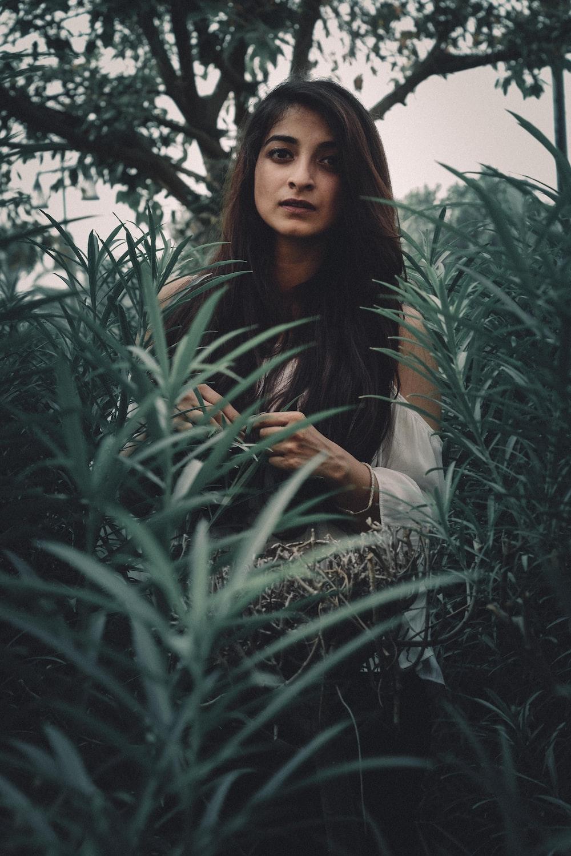 woman standing between green plants