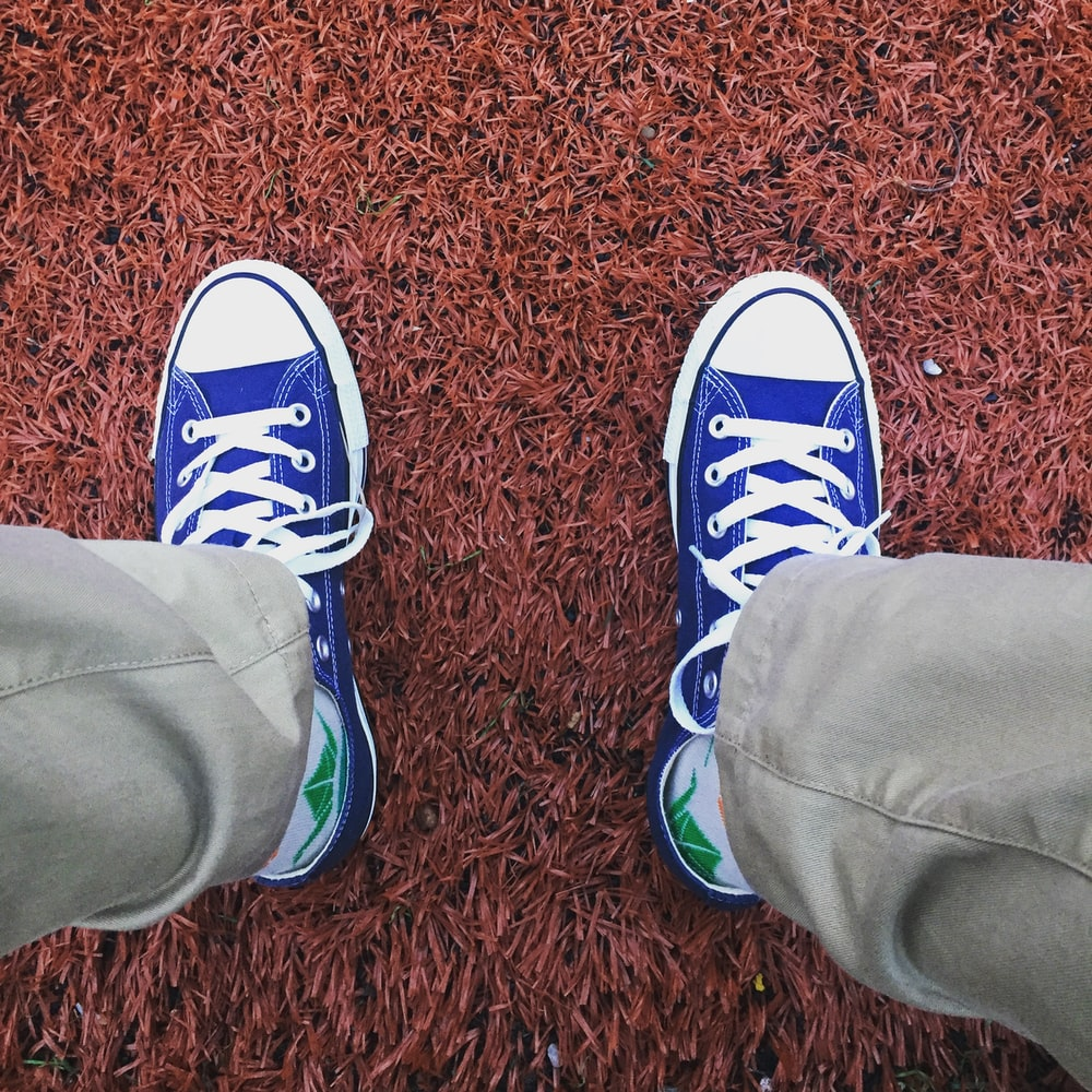 person wearing blue-and-white low-top sneakers