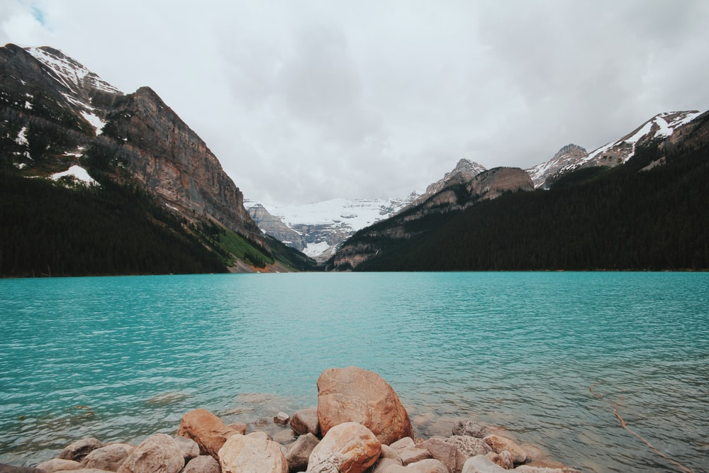 brown rocks beside blue lake near white snowy mountain at daytime