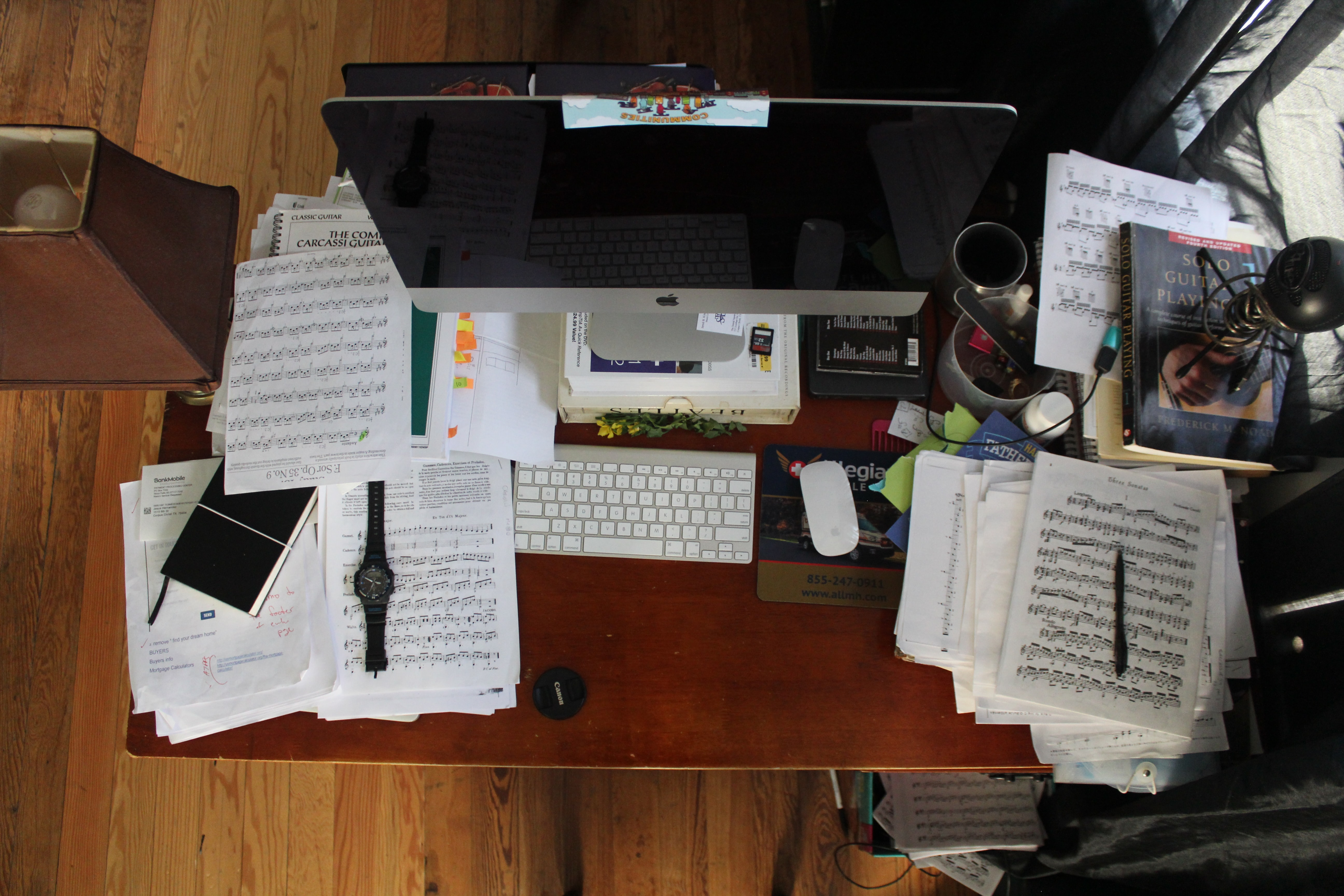 Drone view of messy desk with piles of sheet music and Mac desktop computer and keyboard