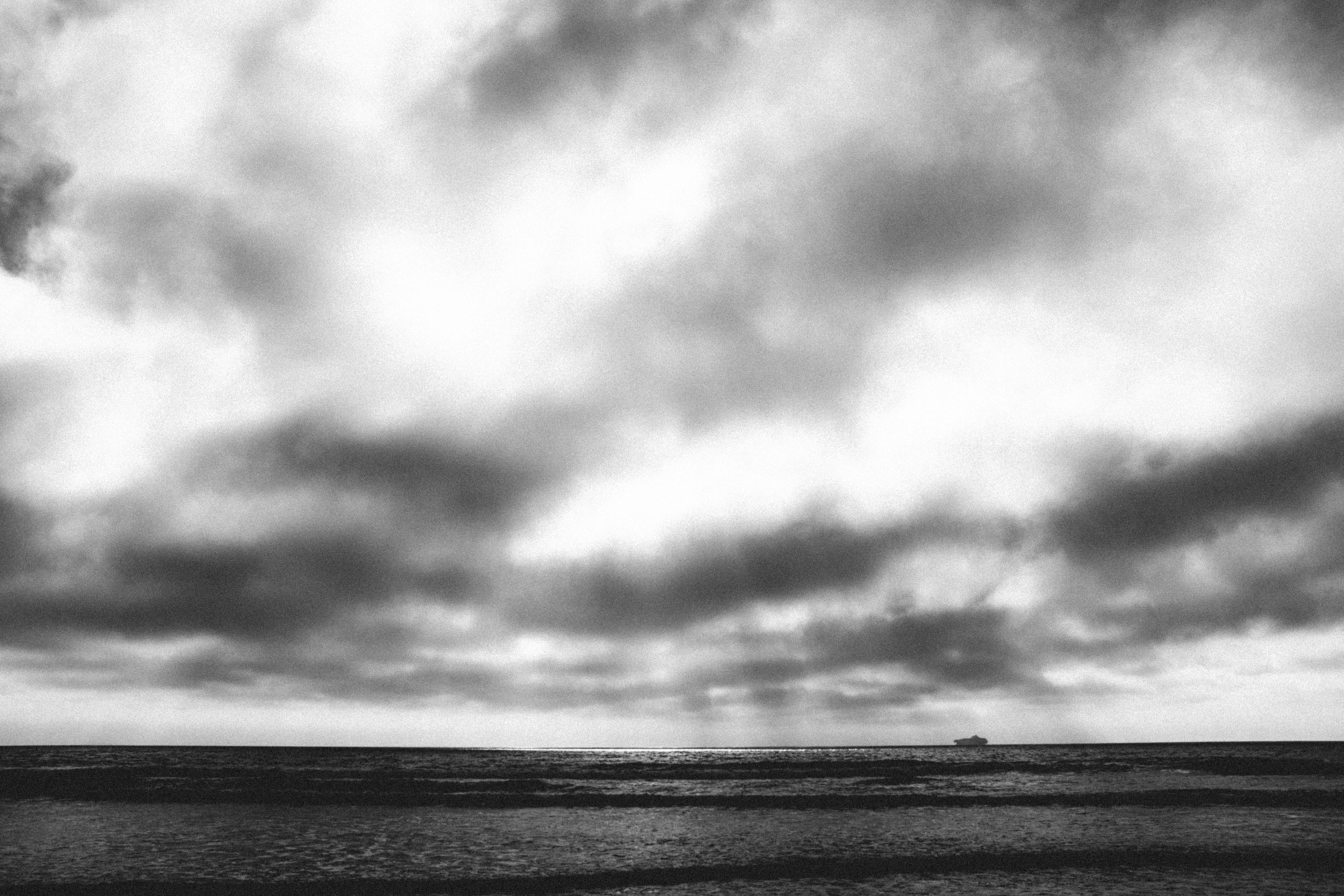 body of water under cloudy sky in grayscale photography