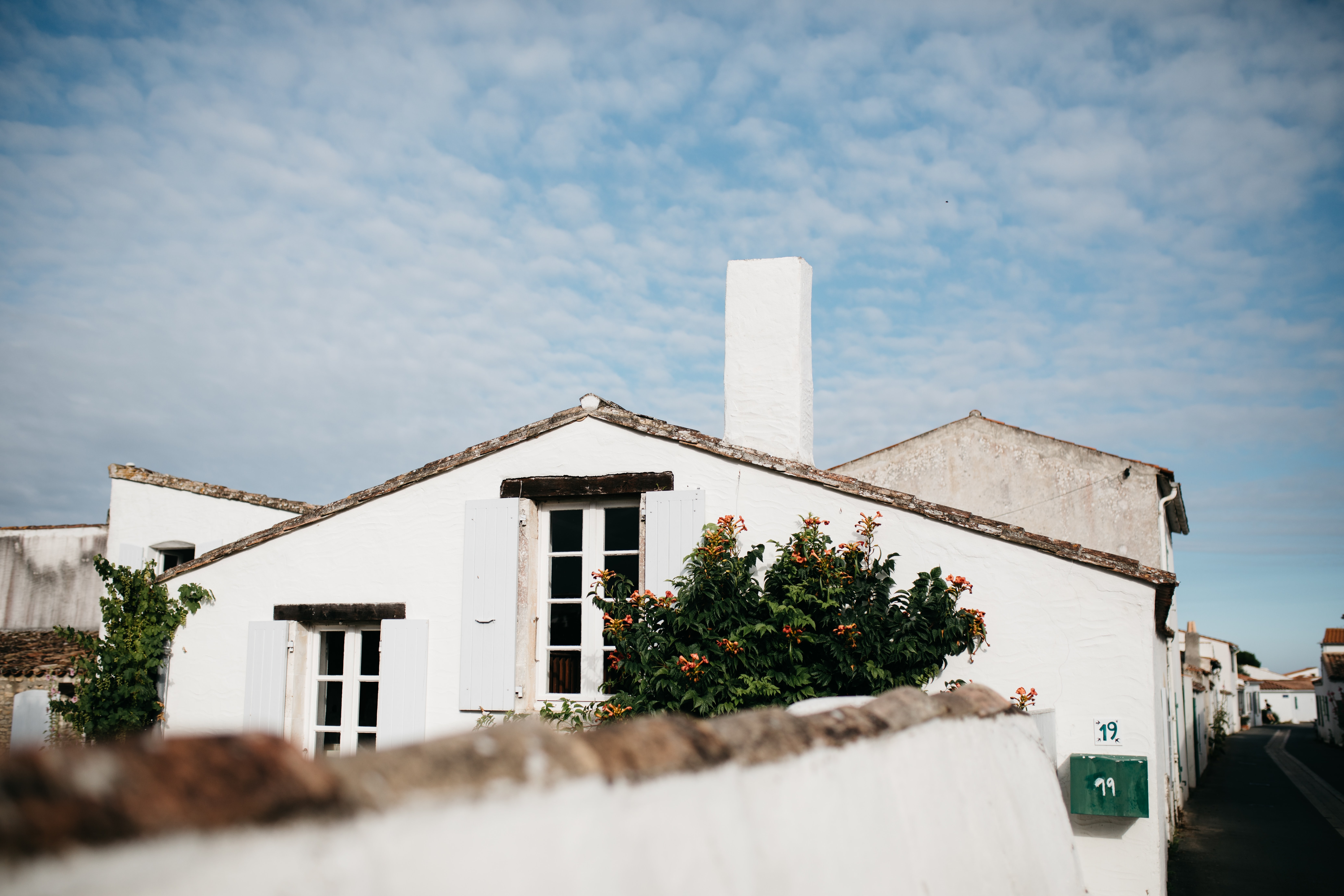 White house in Loix with chimney, windows, and bush in front