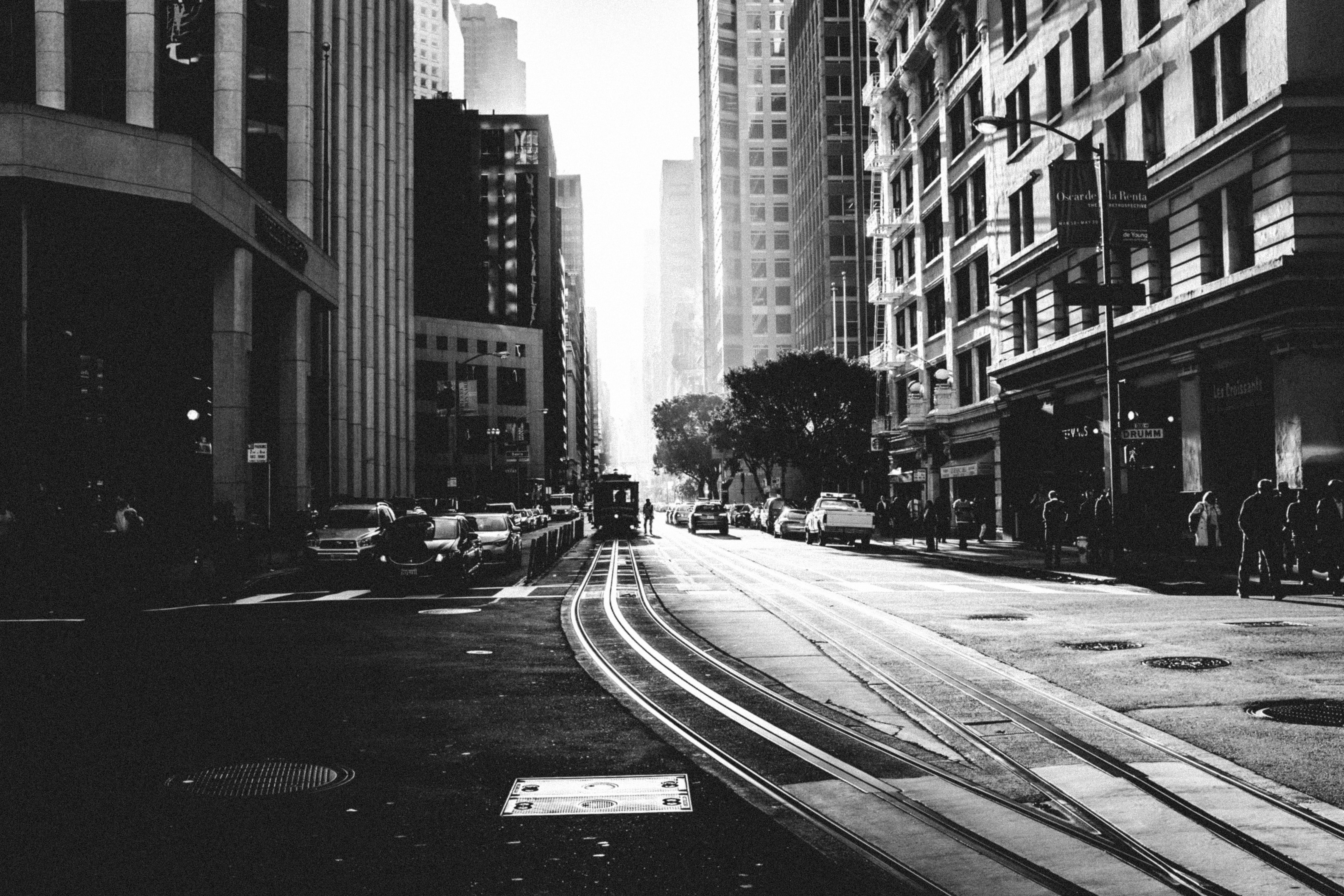 Black and white shot of urban street in San Francisco with people, tramlines and cars
