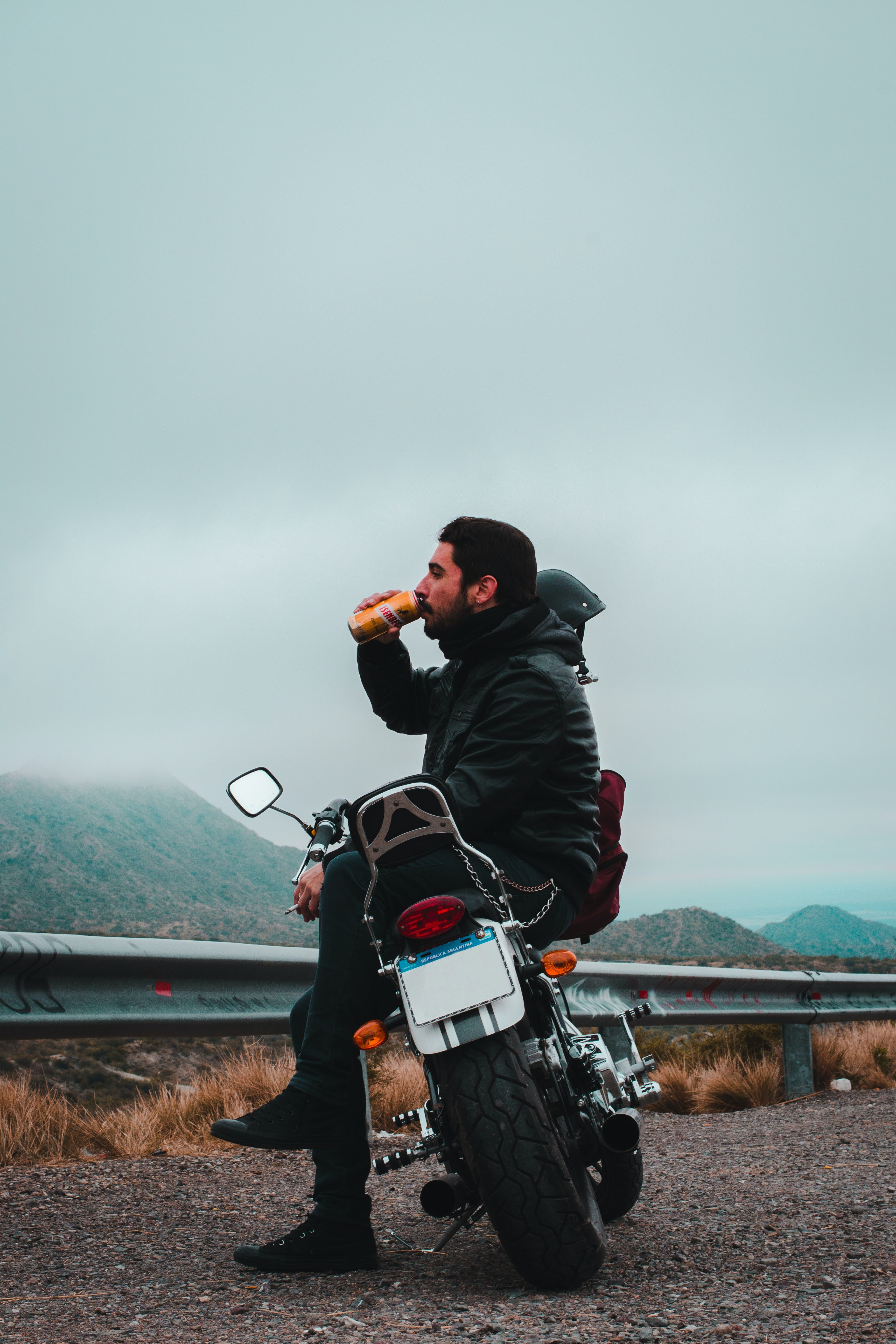 man sitting on motorcycle while drinking beverage in can overlooking mountain under dark cloudy skies at daytime