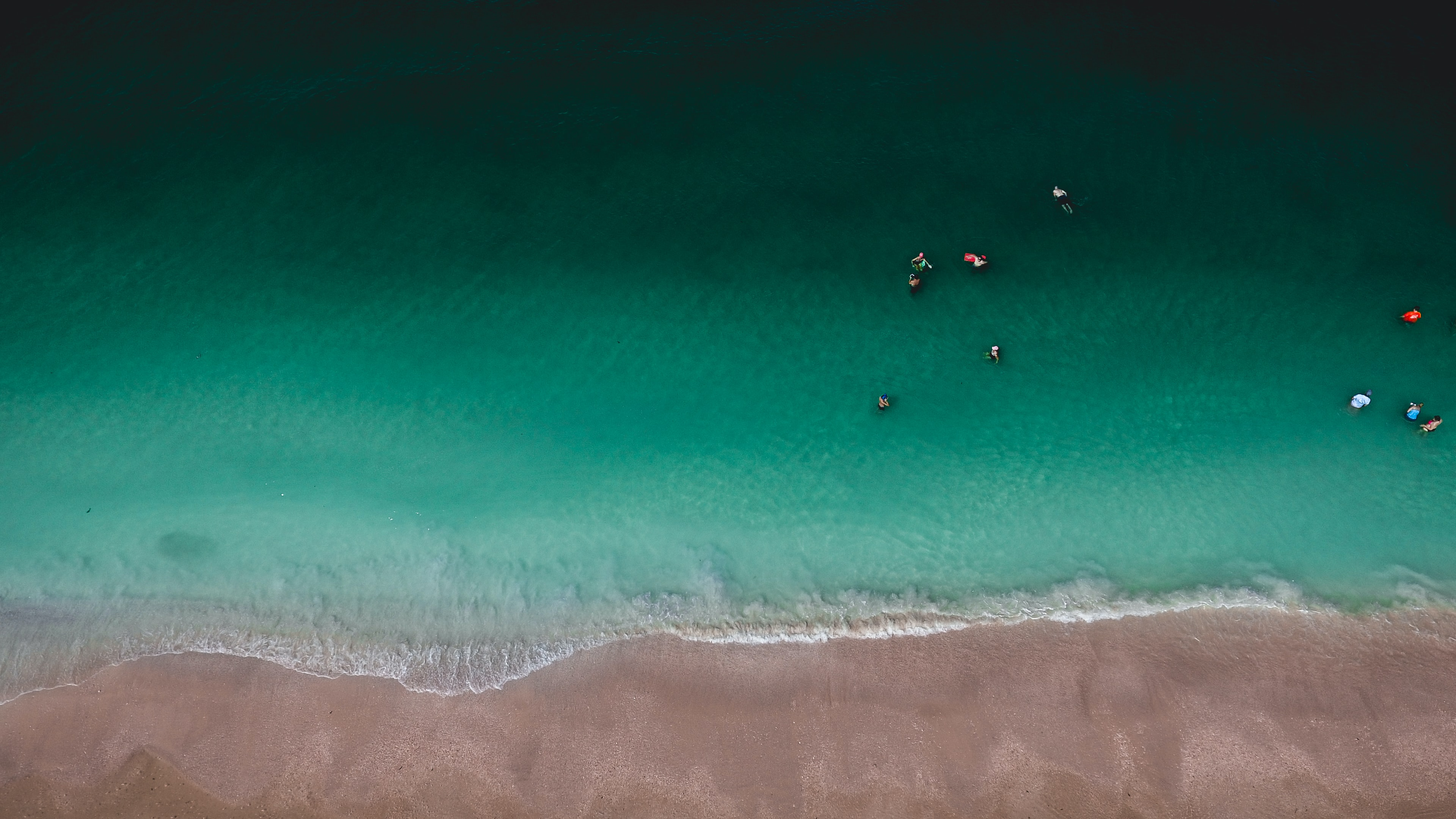 Drone view of the people in the ocean shallow water by the sandy beach at Tigertail Court