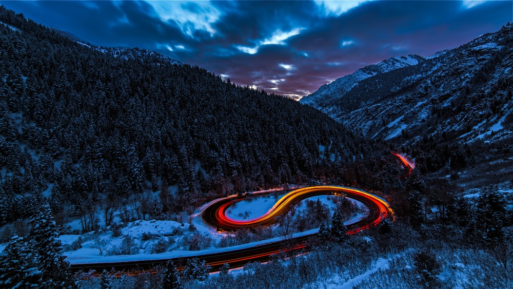 timelapse photography of curved road between mountain with trees