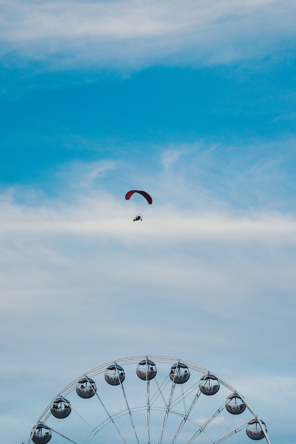 aerial photography of person parachuting above ferris wheel