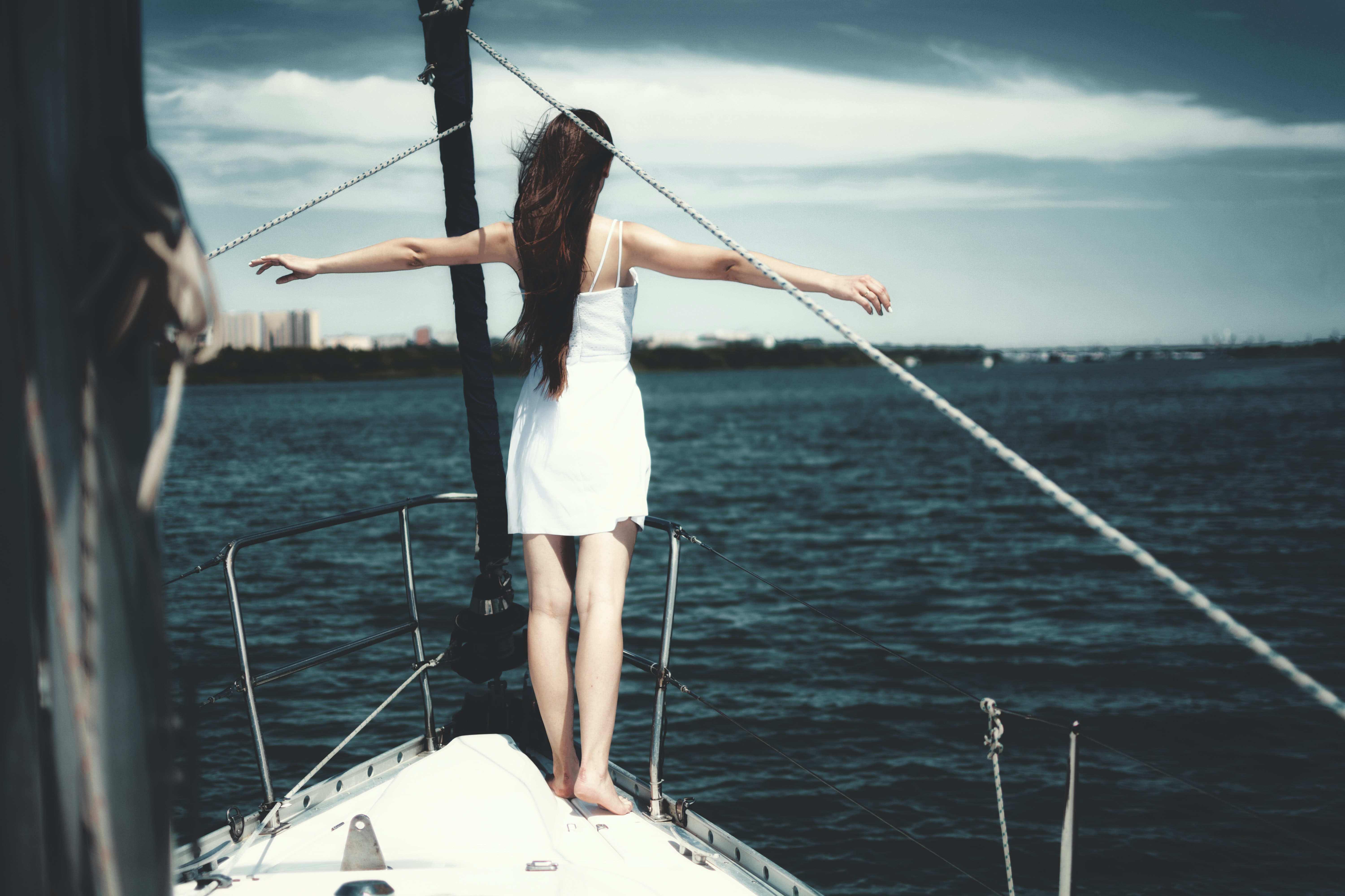 woman standing at the edge of a boat that is sailing in ocean