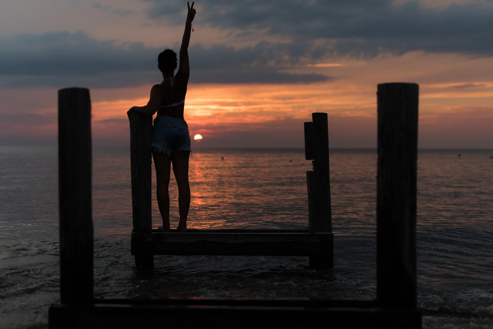 woman standing on brown wooden dock rising her right hand during golden hour