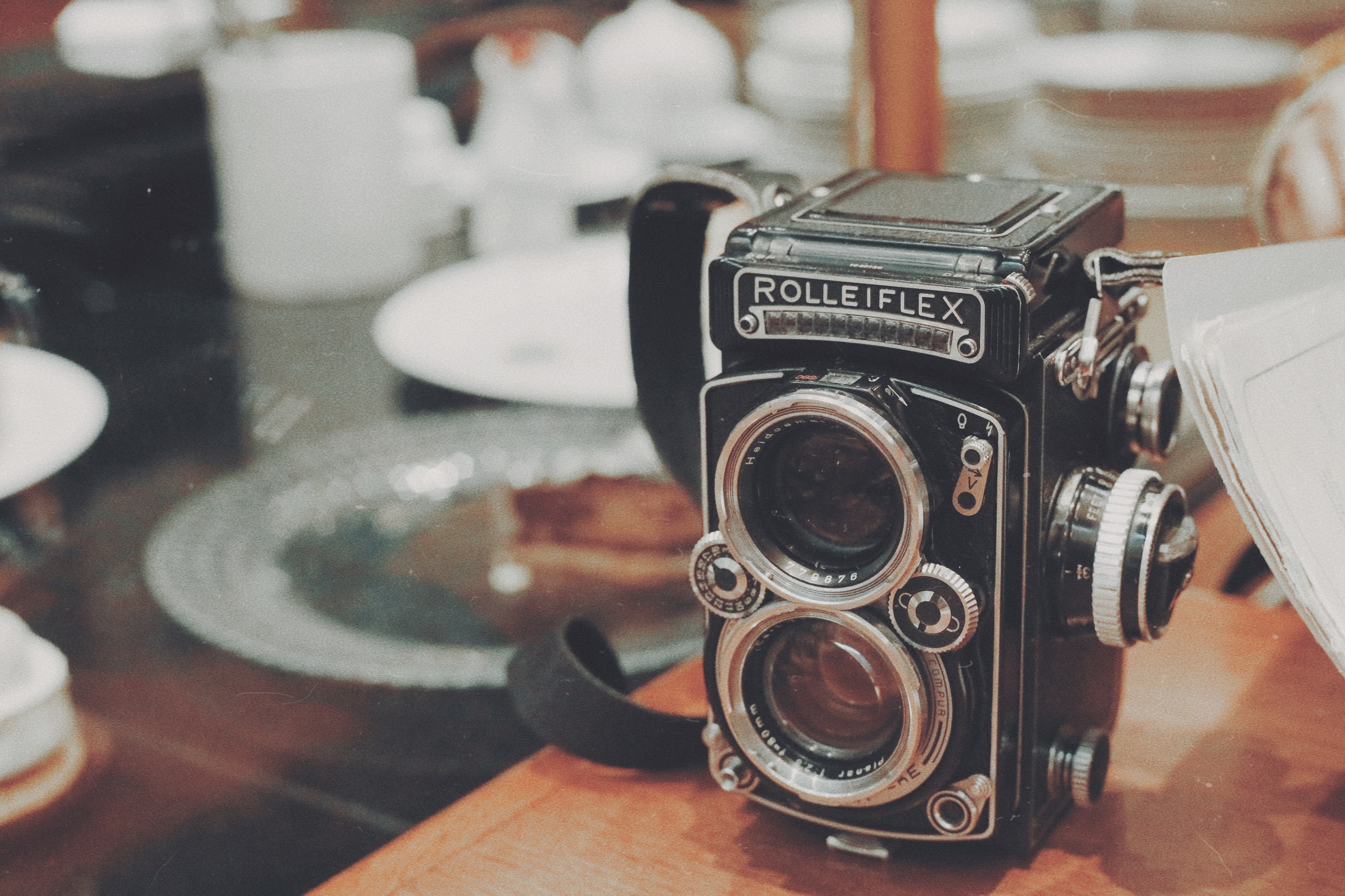 Vintage Rolleiflex camera with strap on glass table with cups