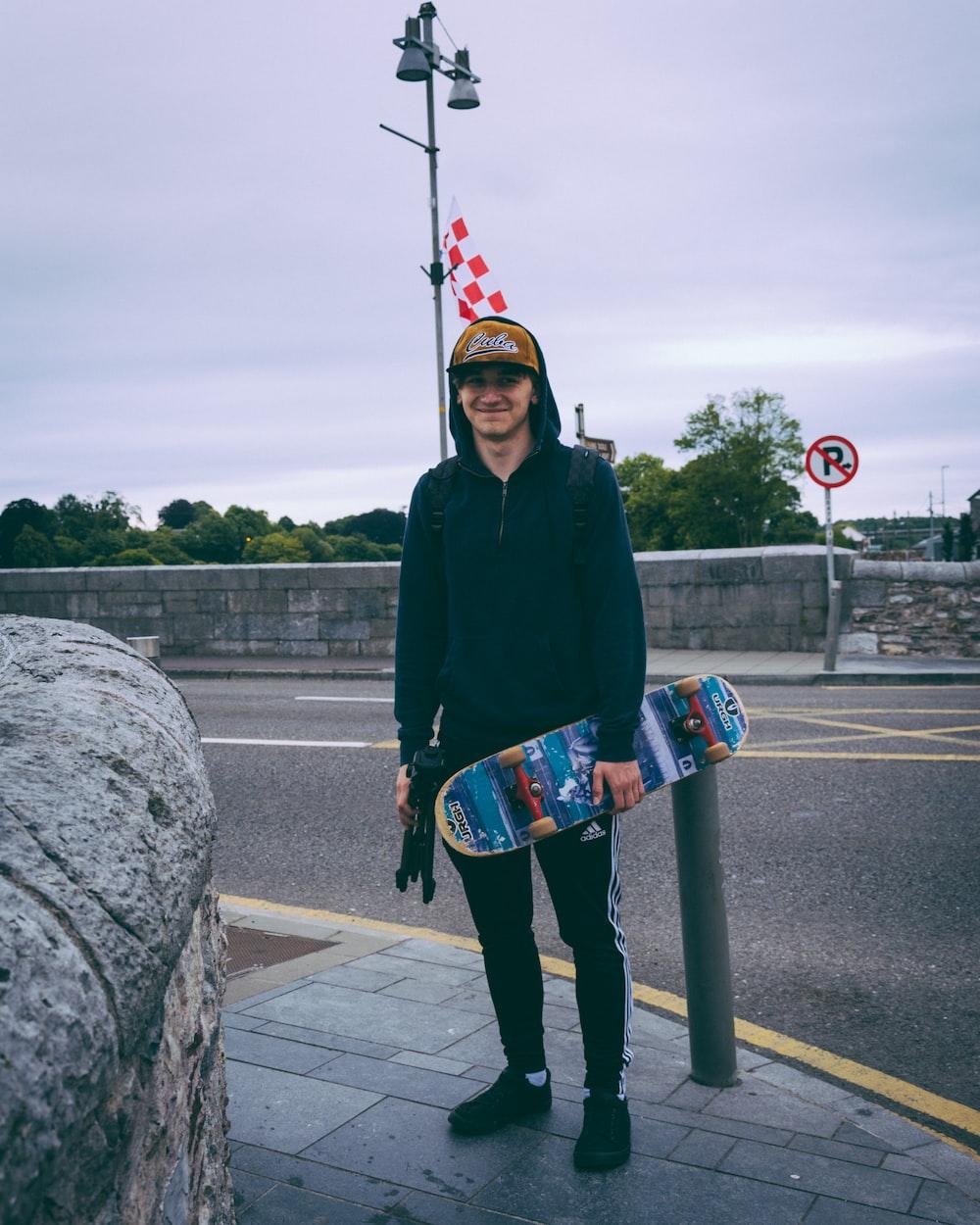 smiling man wearing black hoodie holding skateboard and standing beside bollard across street