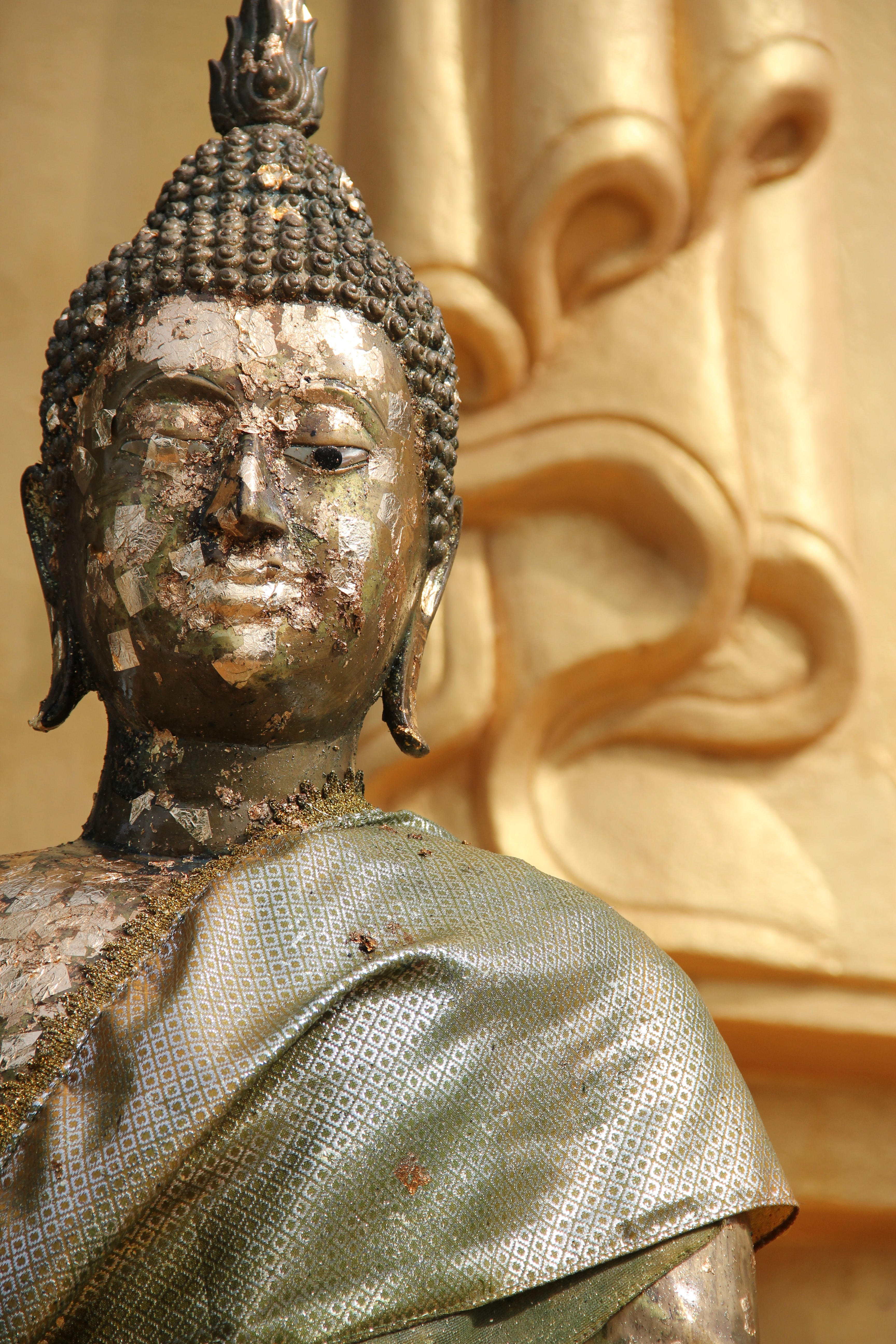 A bronze statue of buddha in front of a gold wall in Khao Tao