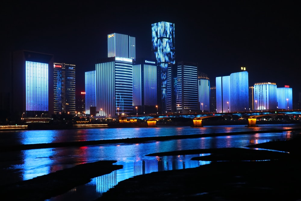 photography of lighted buildings reflecting on water