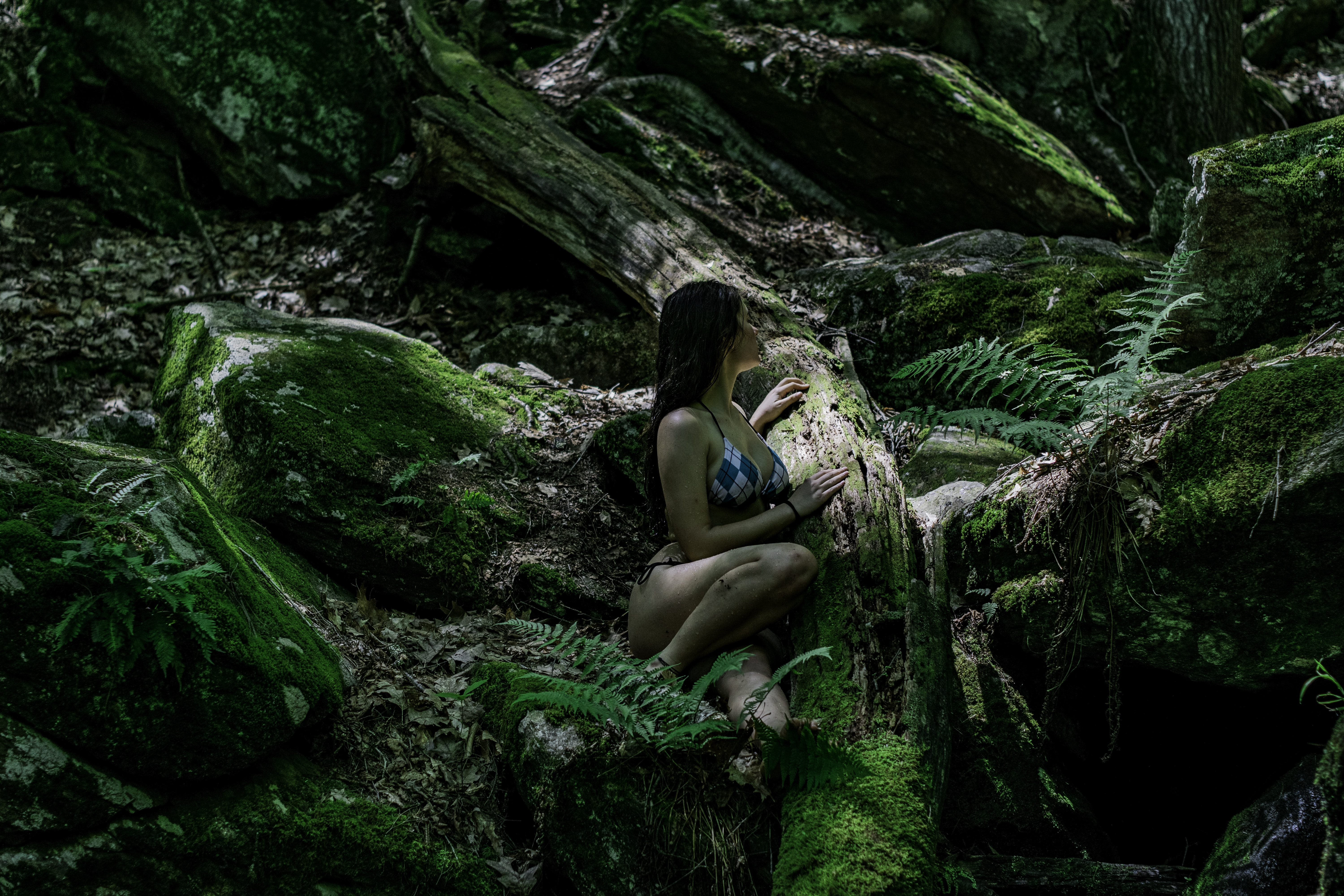 A woman in a bikini among mossy logs and rocks in a forest in Wilton