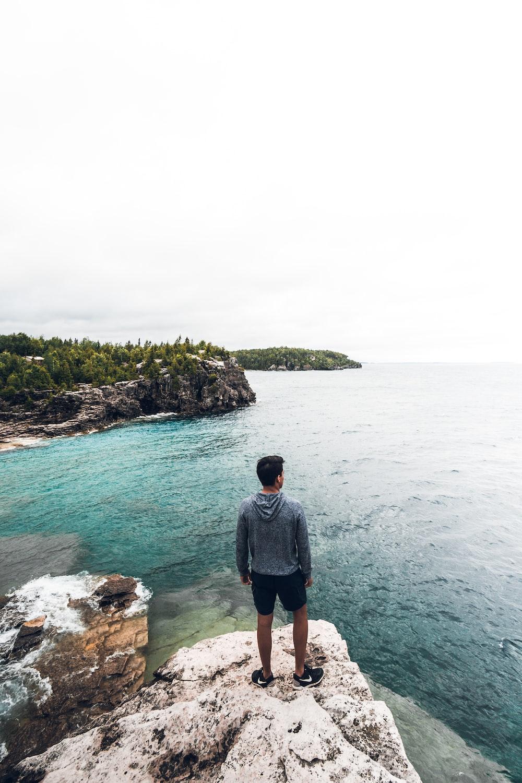 man standing on white and brown rock seeing horizon during daytime