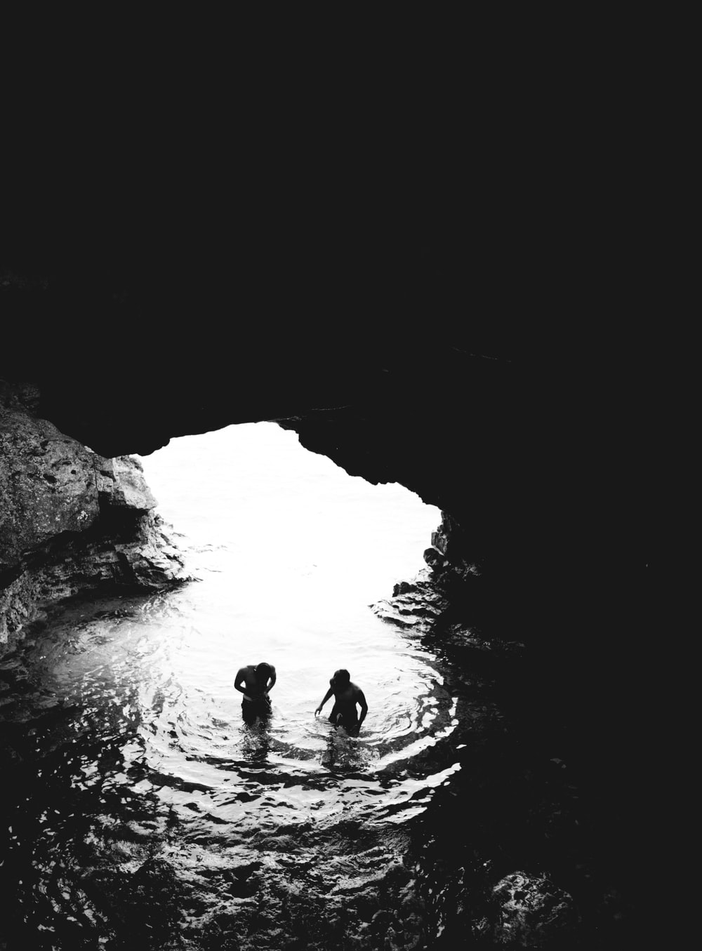 grayscale photo of two men in cave with body of water