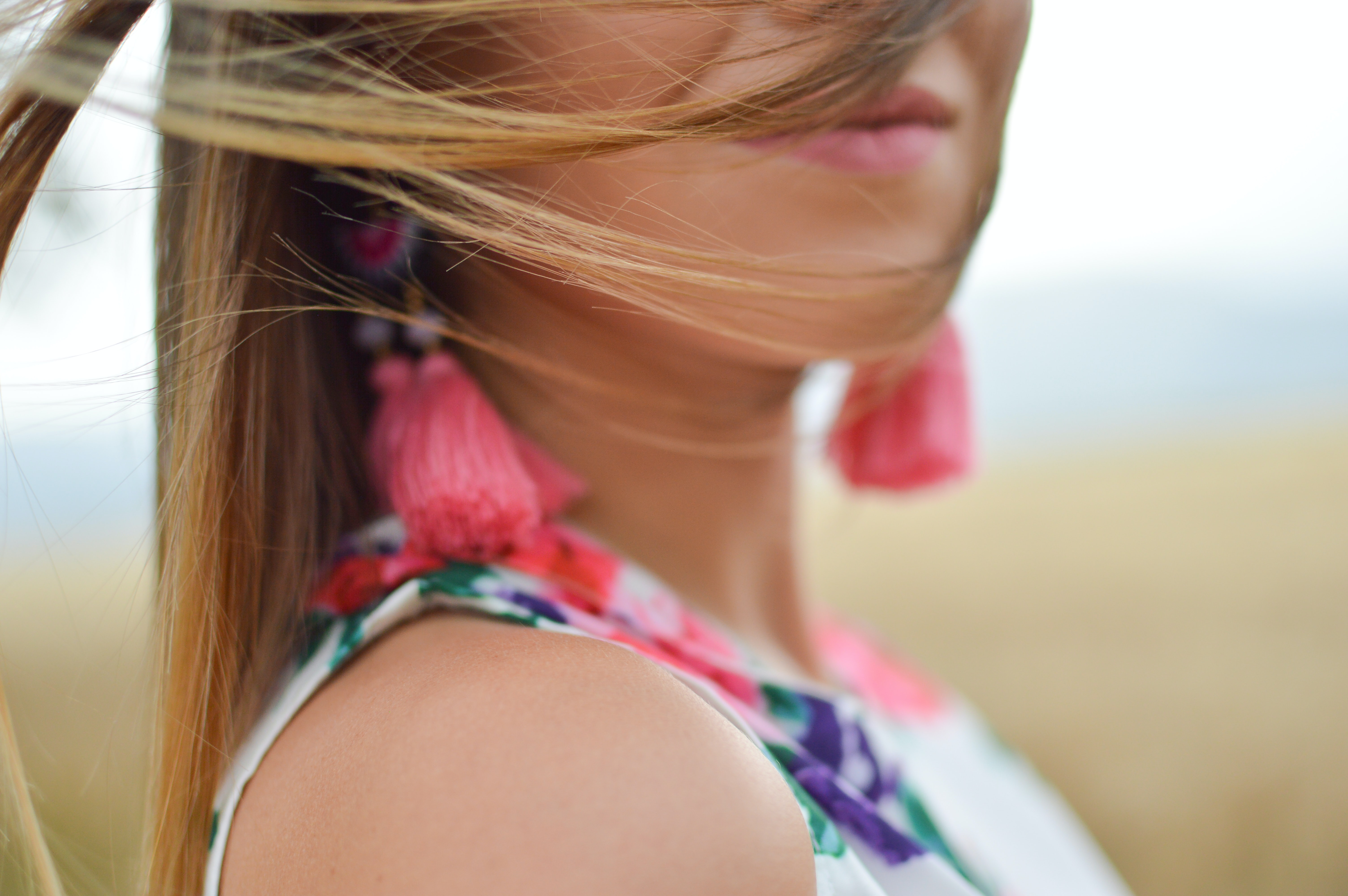 A close-up of a woman with hair over her face and pink fringe earrings