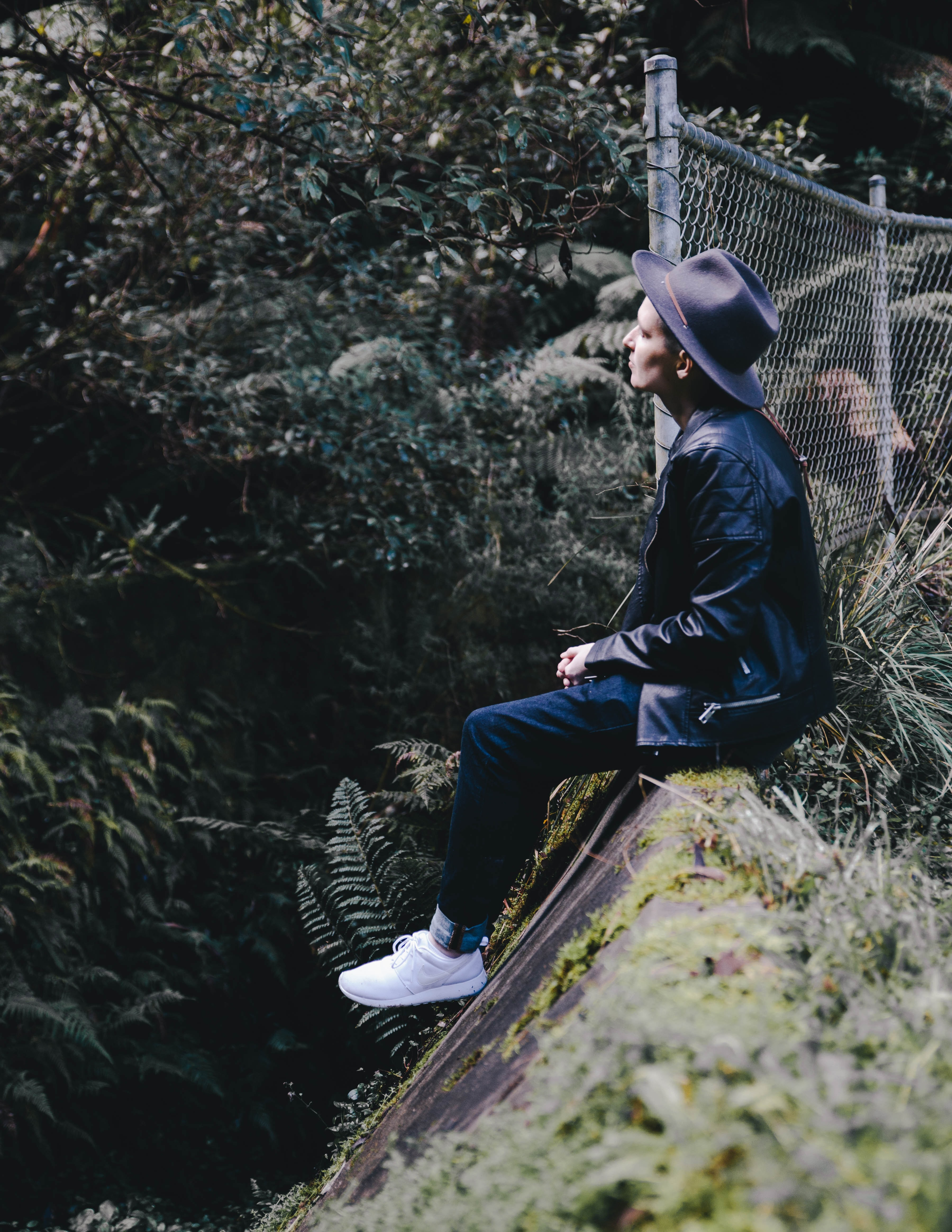 A person in a hat and white sneakers sits by a fence on a steep ledge