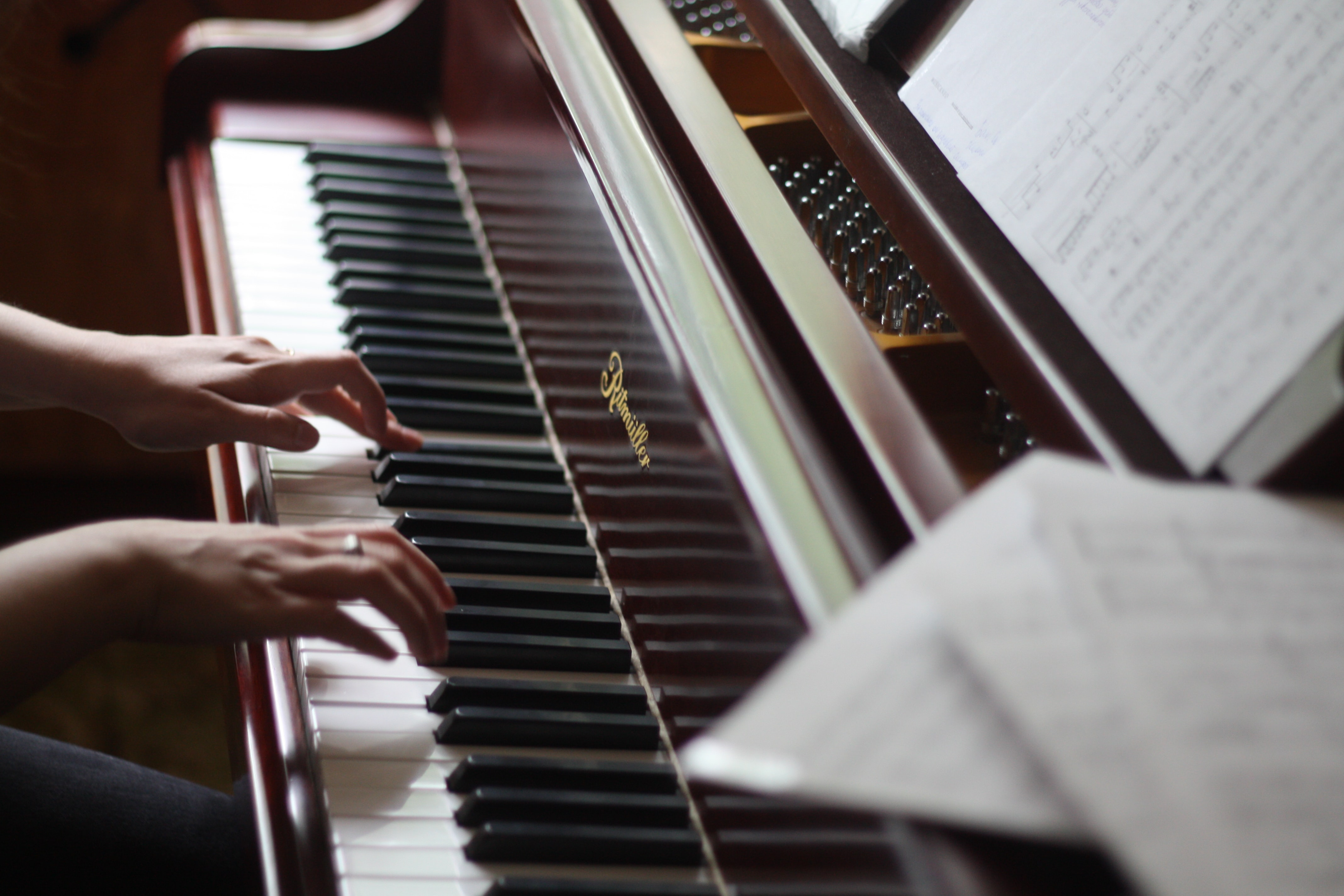 Cropped shot of someone's hands as she plays the piano.