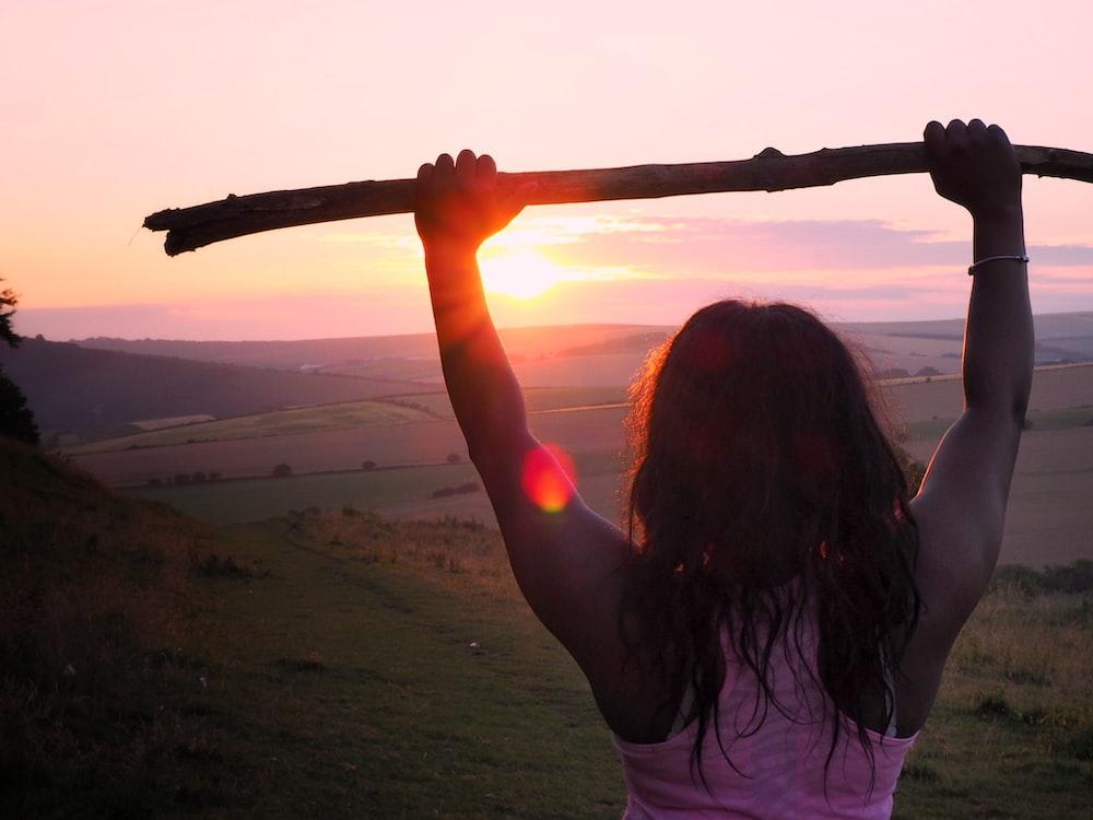 woman wearing pink tank top holding wood stick during sunrise