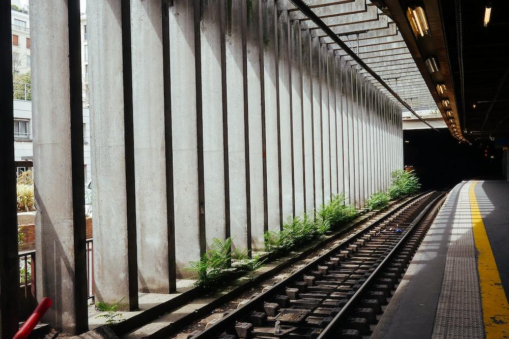 gray concrete road beside train rail