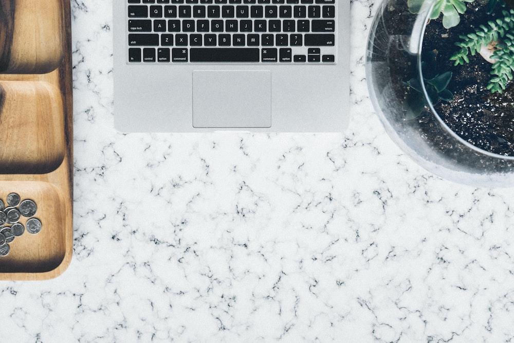 silver MacBook in between jar and tray