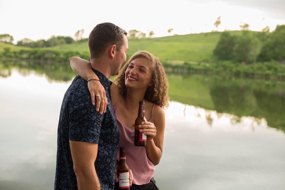 woman holding beer bottle while hugging guy