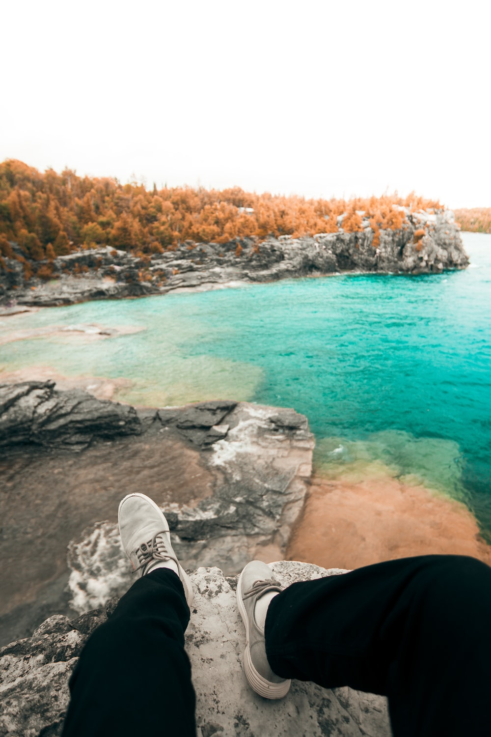 person sitting on cliff viewing body of water during daytime